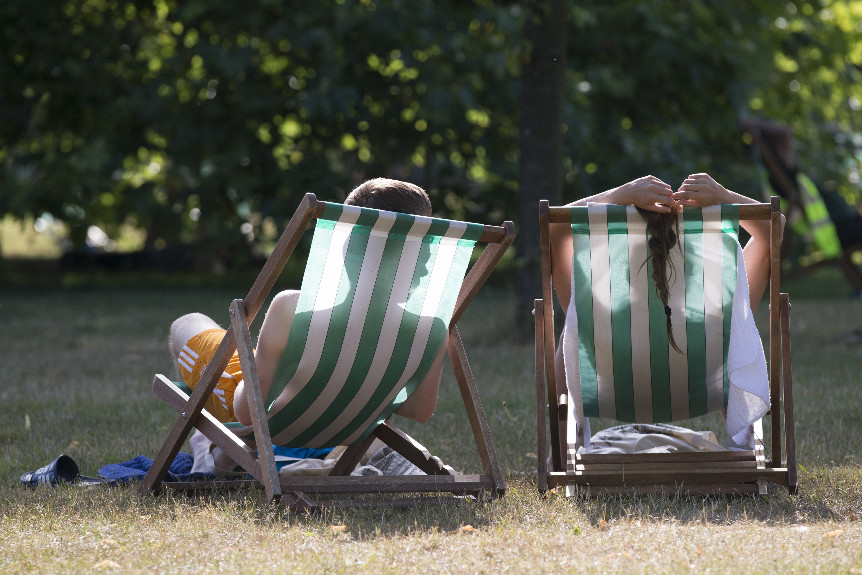 A couple relax on deckchairs in the warm weather in Hyde Park on July 18, 2014 in London as temperatures soar to their highest of the year.