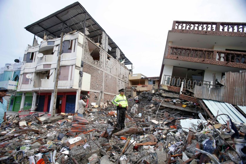 A police officer stands on debris, next to buildings destroyed by an earthquake in Pedernales, Ecuador, Sunday, April 17, 2016. The strongest earthquake to hit Ecuador in decades flattened buildings and buckled highways along its Pacific coast, sending the Andean nation into a state of emergency. (AP Photo/Dolores Ochoa)