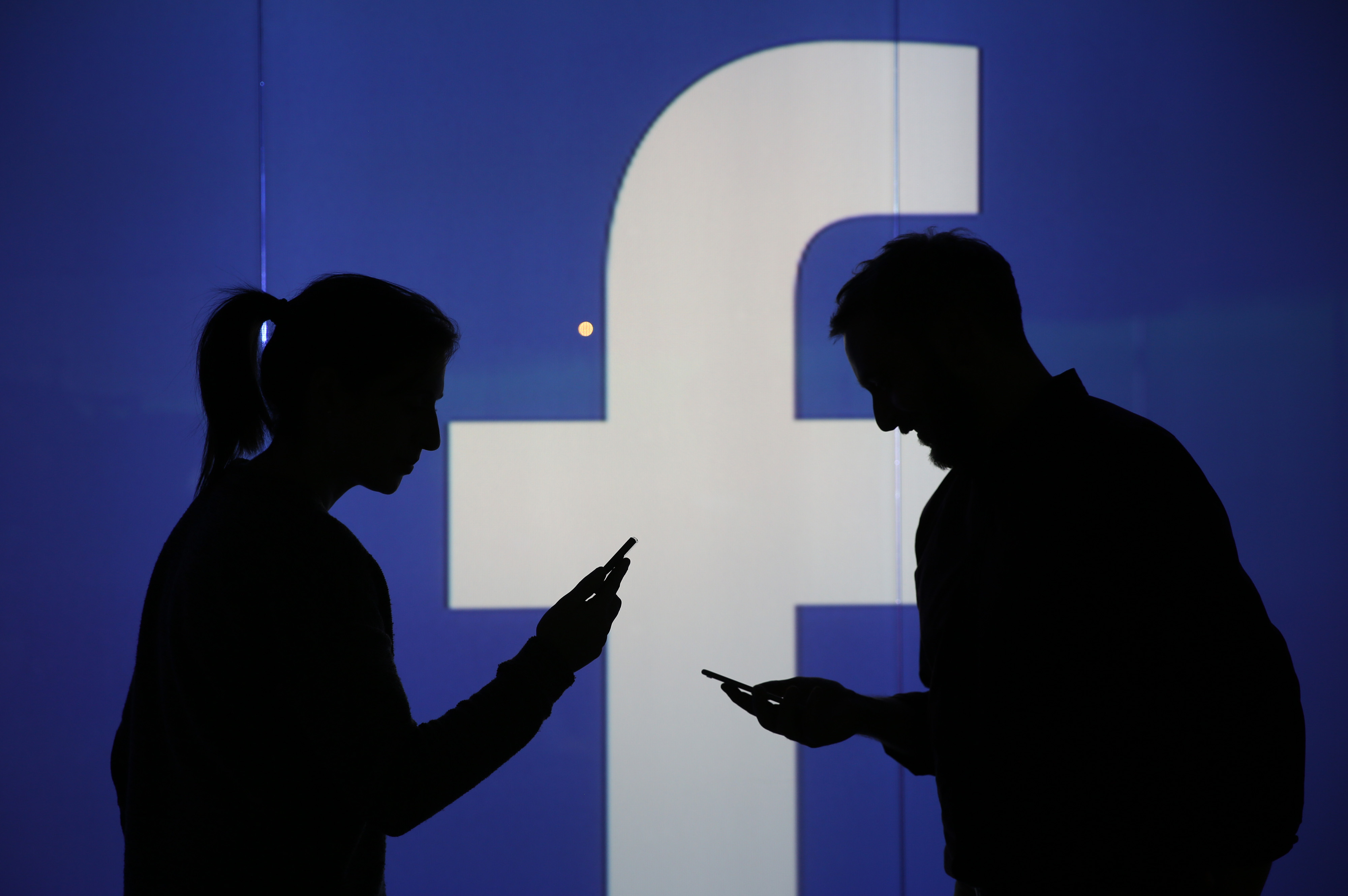 People are seen as silhouettes as they check mobile devices whilst standing against an illuminated wall bearing Facebook Inc.s logo in this arranged photograph in London, on Dec. 23, 2015.