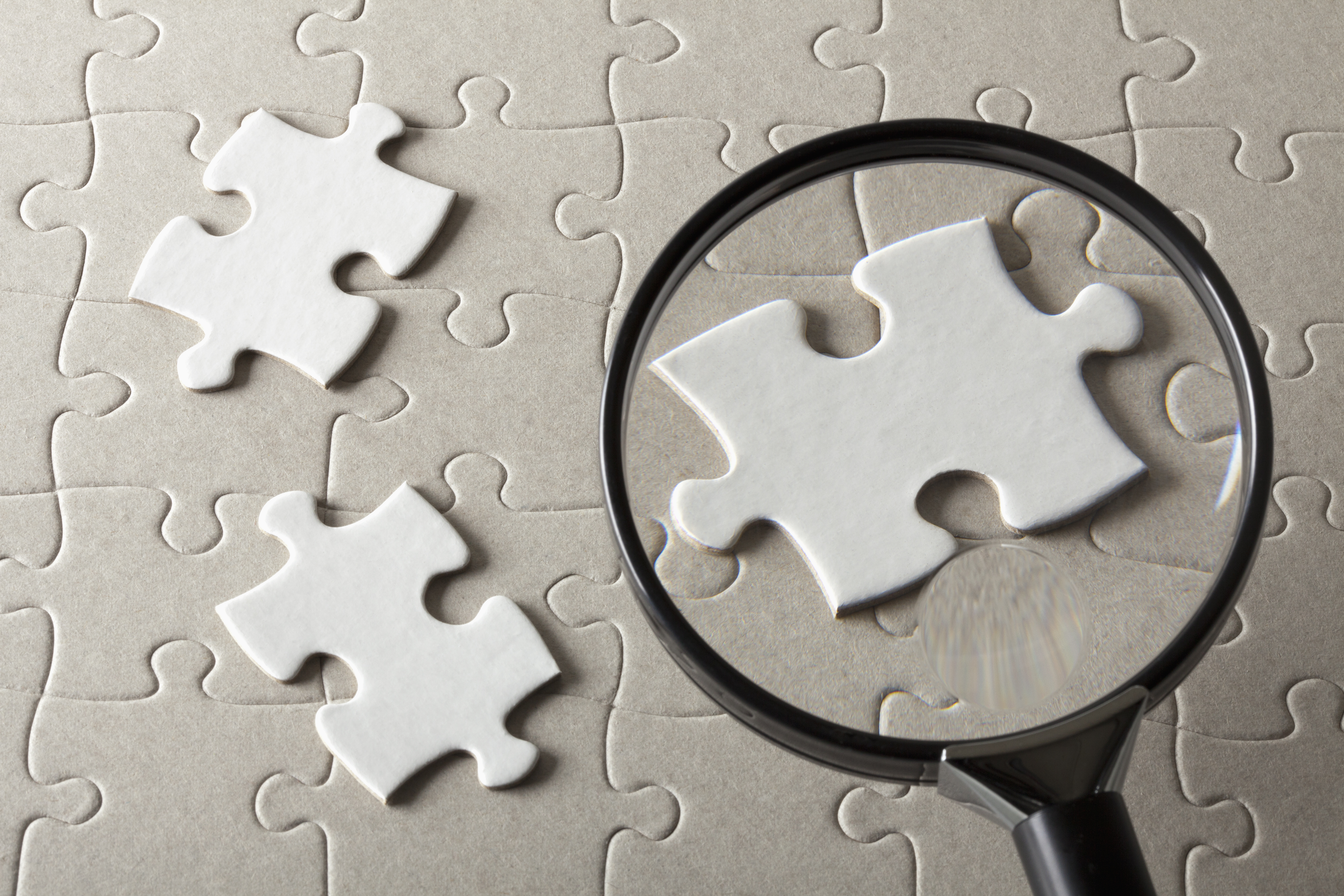Puzzle pieces on a jigsaw puzzle being magnified by a magnifying glass