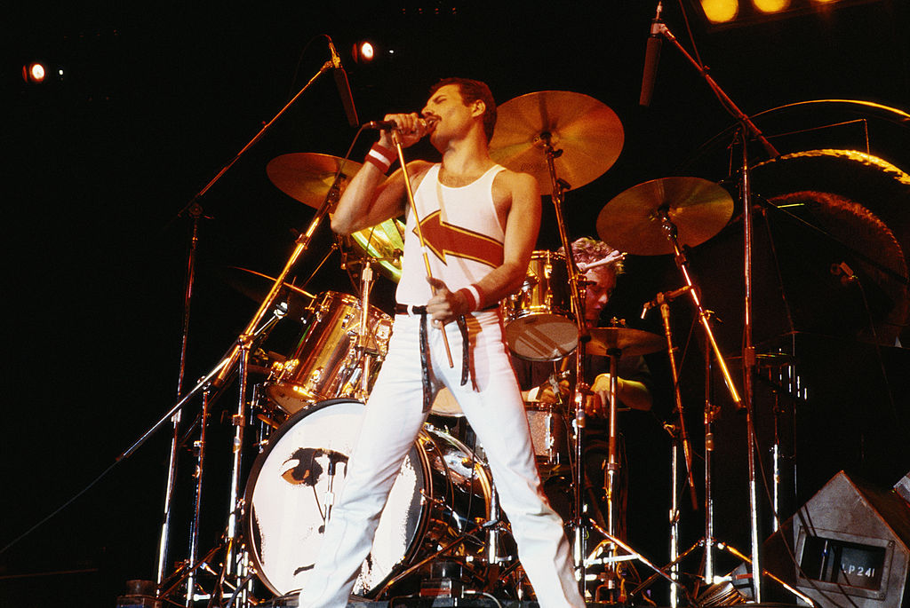 Freddie Mercury (1946-1991), singer with Queen, standing in front of a drumkit as he sings into a microphone on stage during a live concert performance by the band at the National Bowl in Milton Keynes, England, United Kingdom, in 1982.