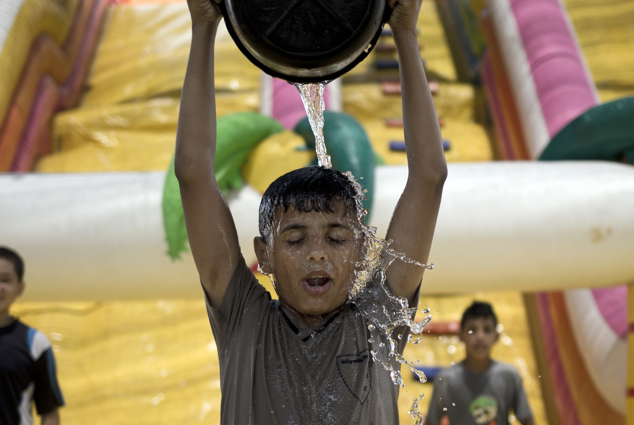 A Palestinian boy empties a bucket of water on his head in Gaza City on Aug. 3, 2015, during a sweltering heat wave.