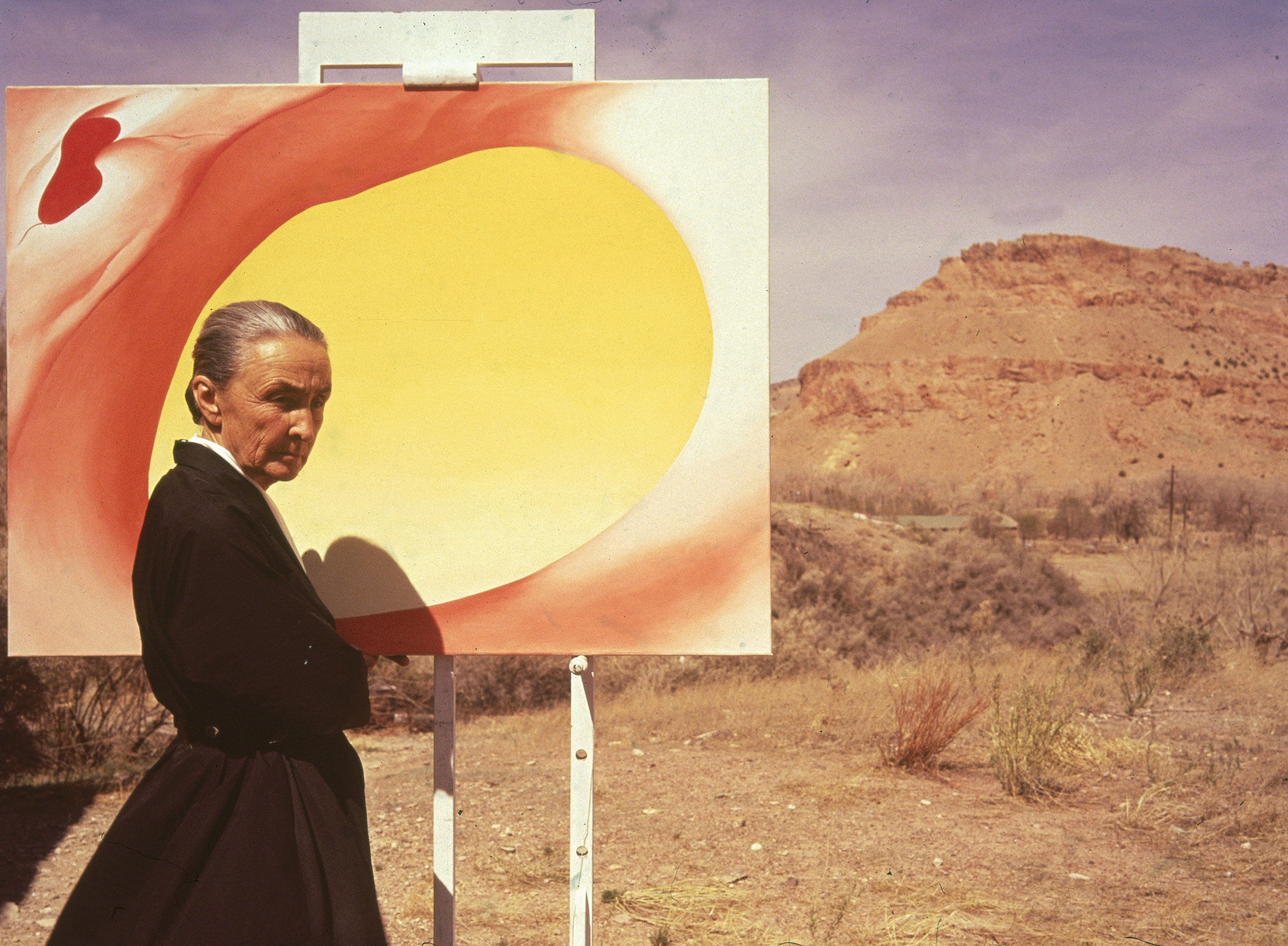 American artist Georgia O'Keeffe (1887 - 1986) poses outdoors beside an easel with a canvas from her series, 'Pelvis Series Red With Yellow,'  Albuquerque, New Mexico, 1960.