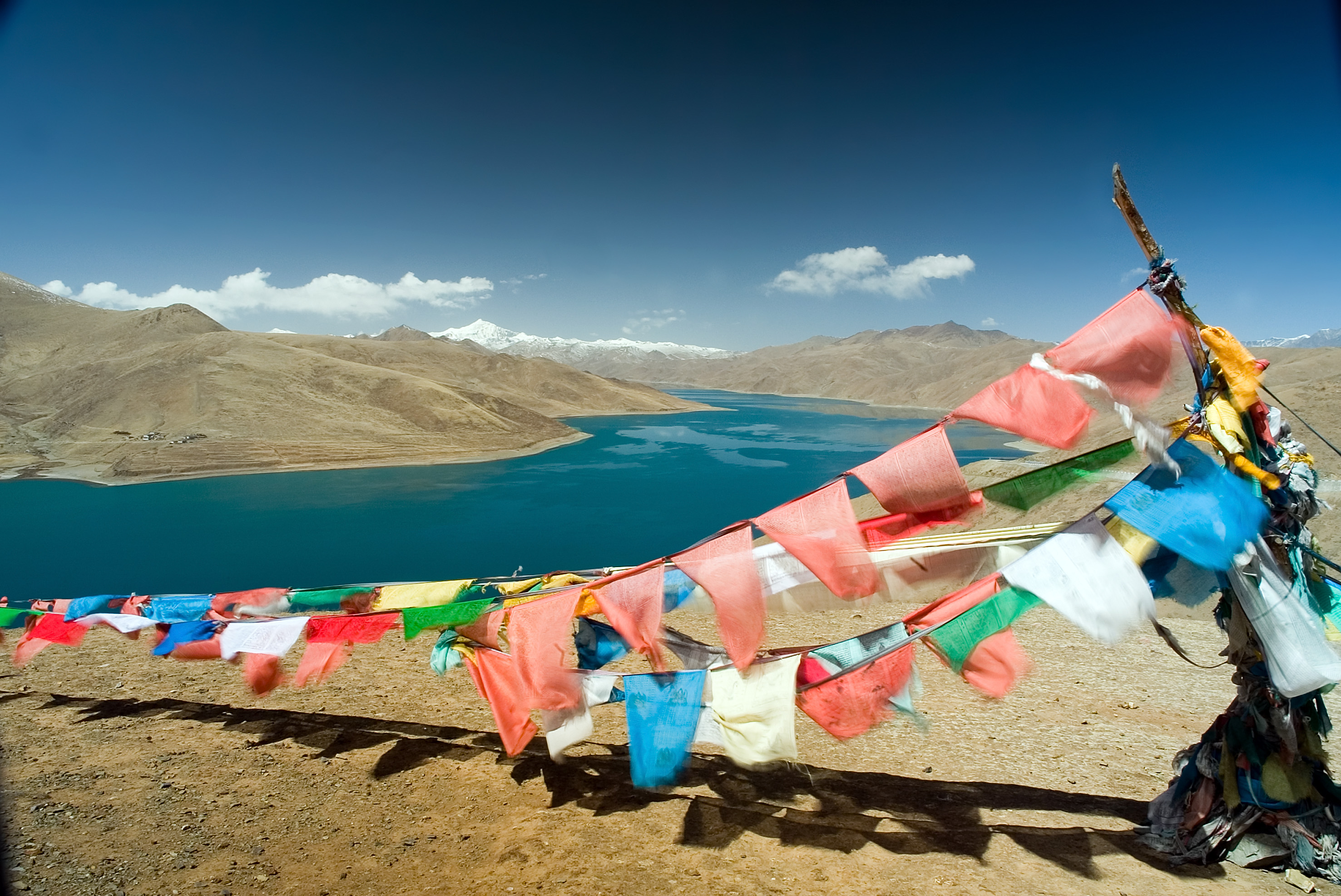 Buddhist prayer flags flutter at a pass overlooking Yamdrok Lake, which is considered one of Tibet's holy lakes. The lake sits at an altitude of more than 13,000 ft.