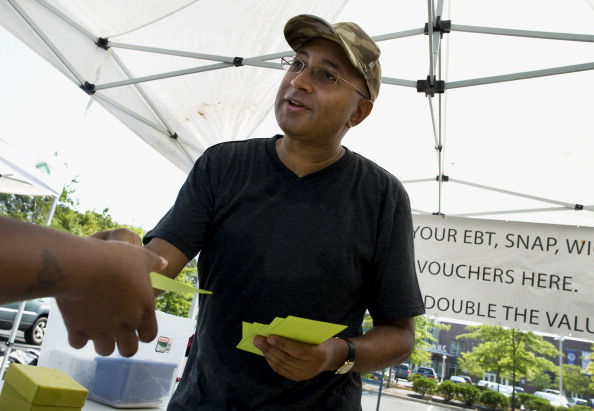WASHINGTON, DC- JULY 28: John Gloster gives WIC Coupons to a customer to use at the Ward 8 Farmers Market Cooperative on Saturday, July 28th, 2012. Joh is President of the Ward 8 Farmers Market Cooperative.  (Photo by Tracy A. Woodward/The Washington Post via Getty Images)