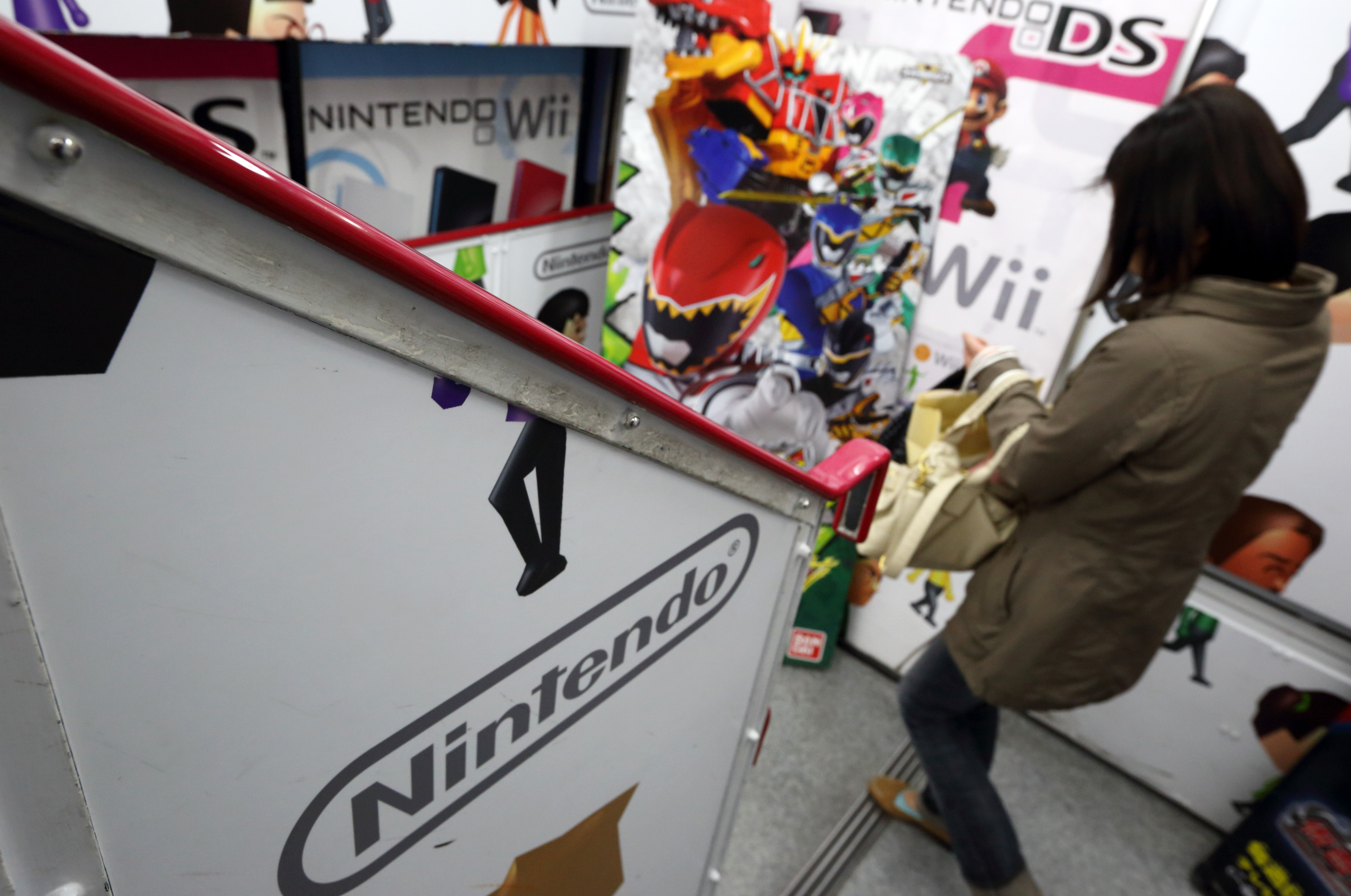 A woman walks past the Nintendo Co. logo displayed at an electronics store in Tokyo, Japan, on Tuesday, April 23, 2013.