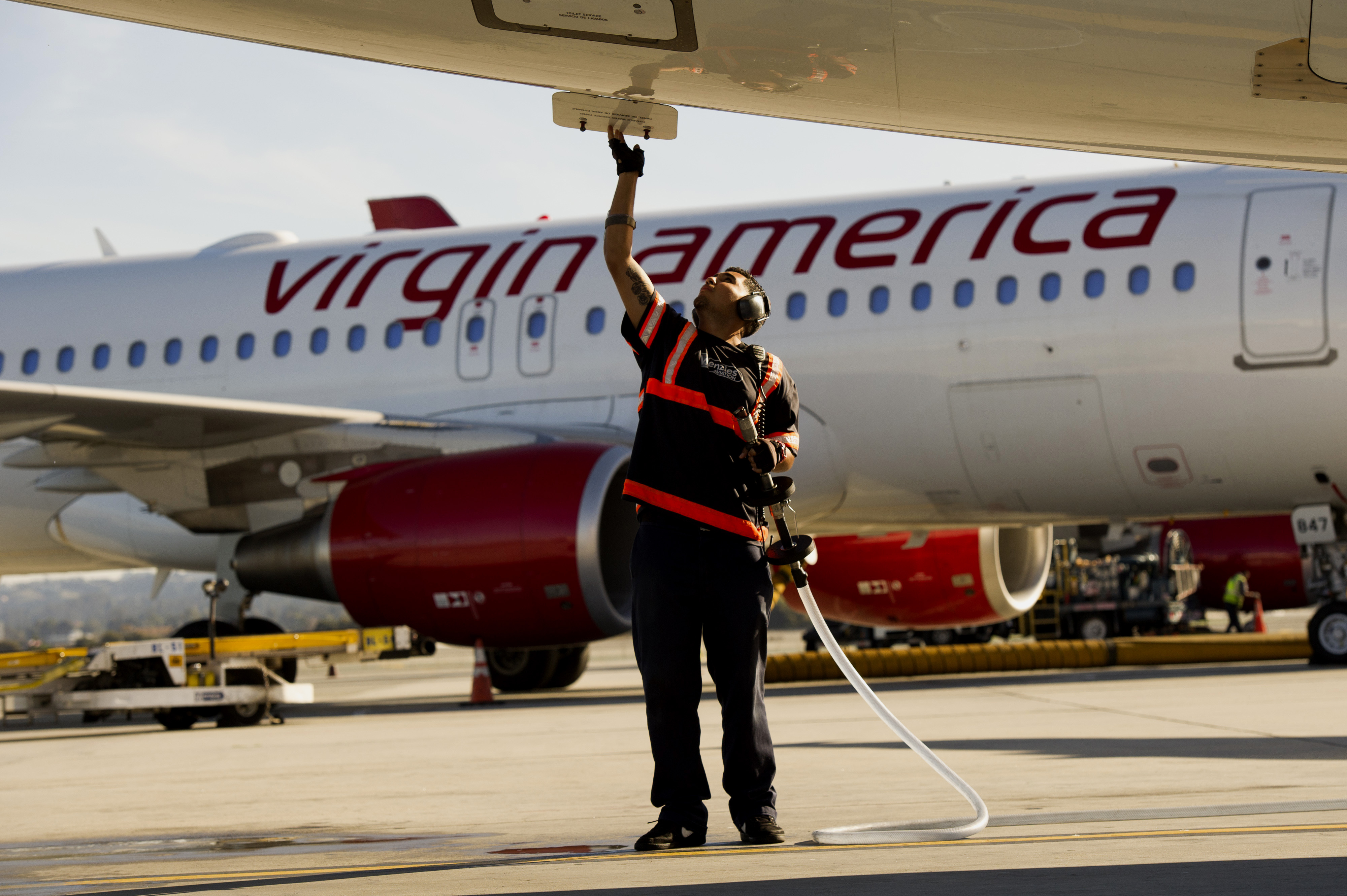 An employee prepares a Virgin America Inc. Airbus A320 plane for take off at San Francisco International Airport (SFO) in San Francisco, California, U.S., on Thursday, Nov. 6, 2014.