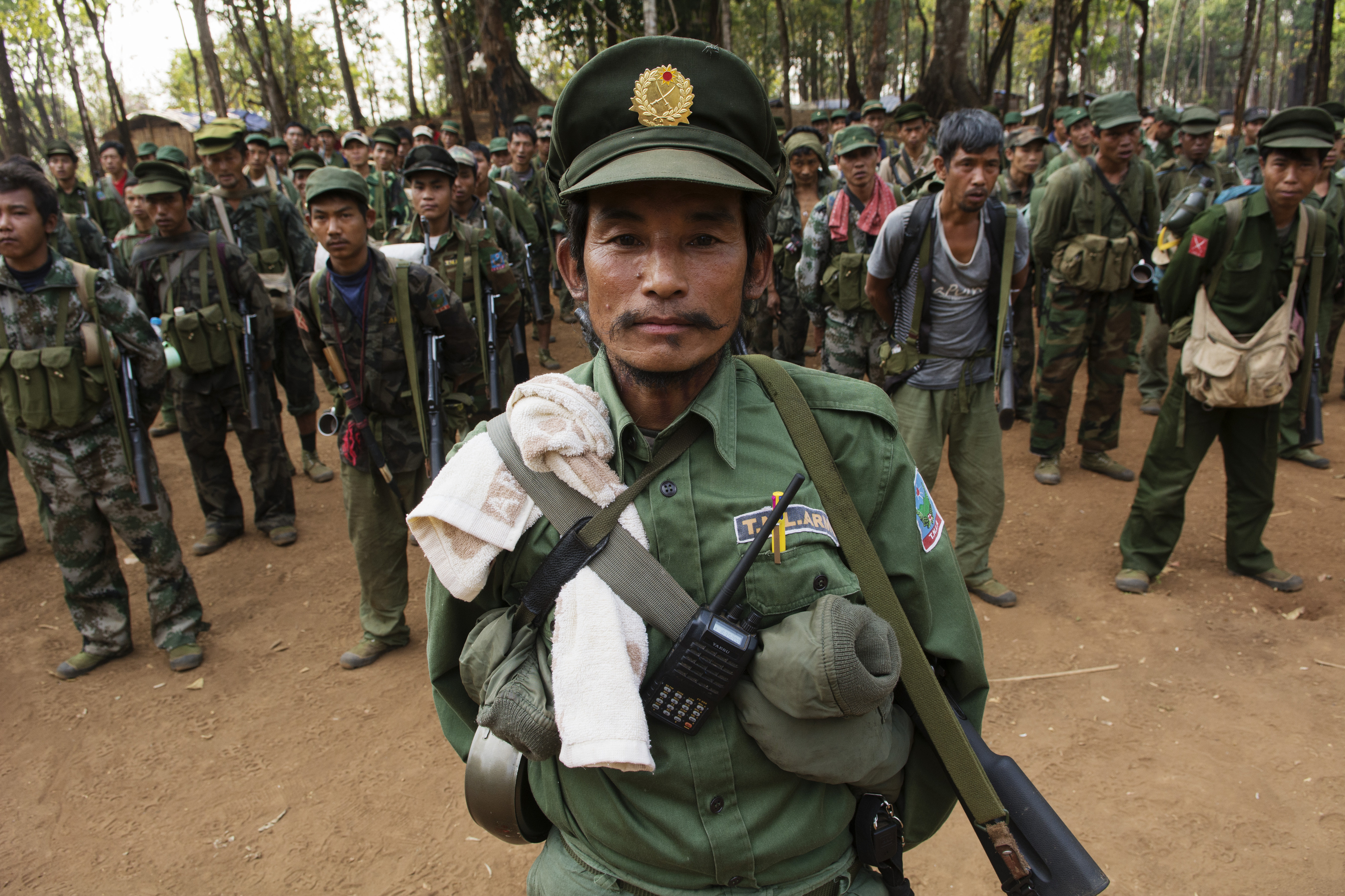 An officer from the Ta'ang National Liberation Army stands at attention with his soldiers during a morning gathering in a military camp