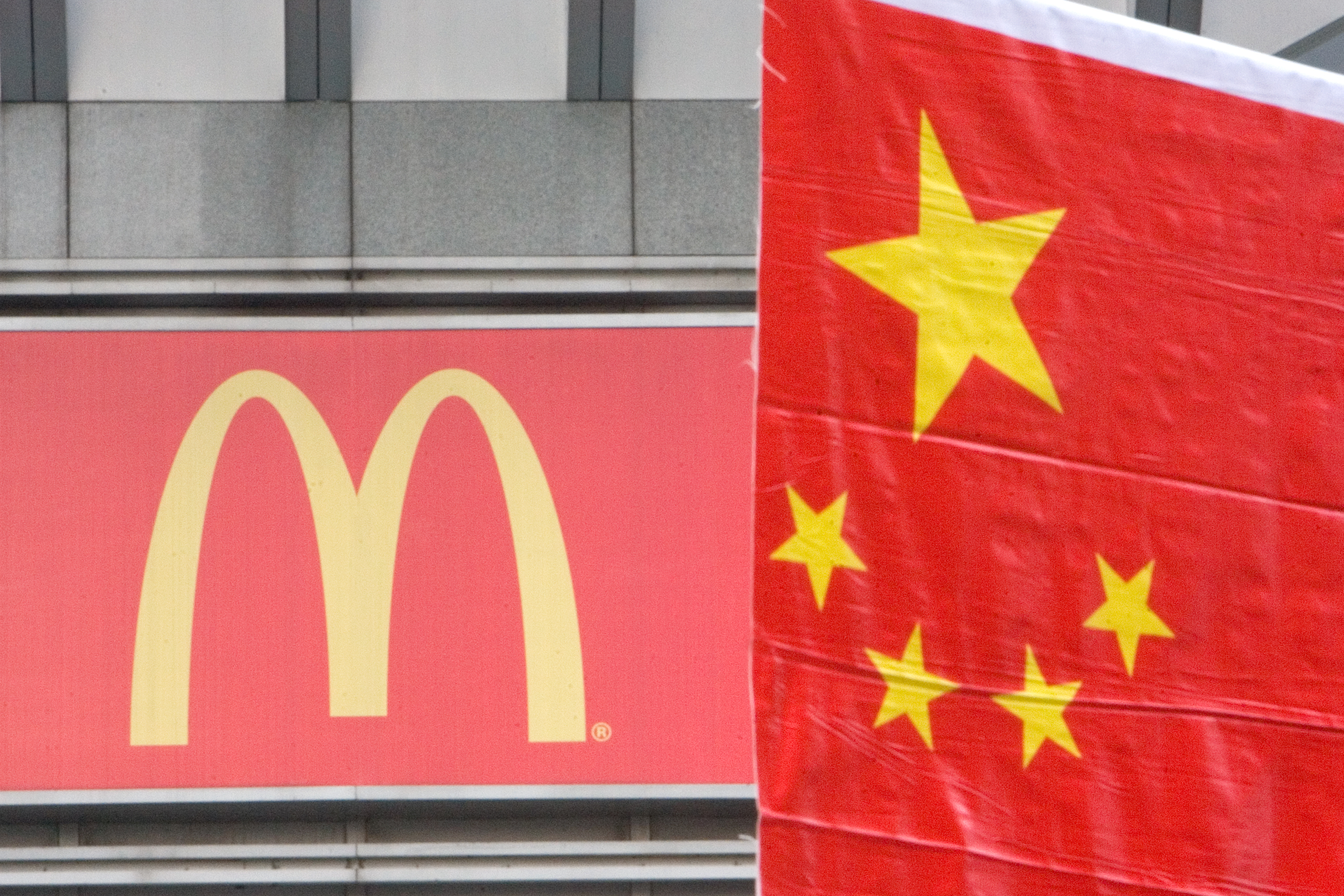 A Chinese flag is put up on Sept. 30, 2007, in Shanghai by a McDonald's sign for a celebration of China's National Day on Oct. 1