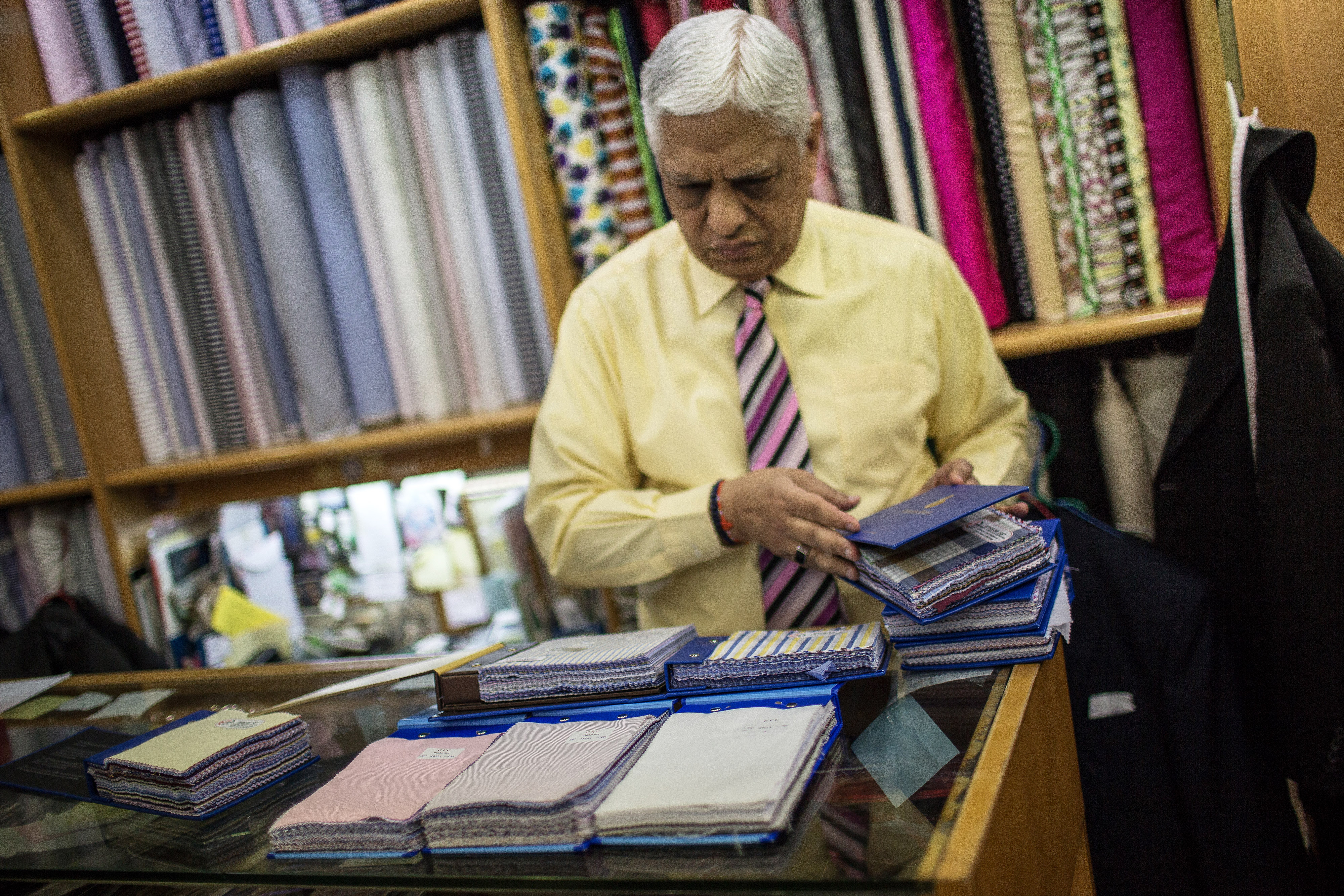 Manu Melwani, co-owner of Sam's Tailor, arranges fabric samples at the company's store in the Tsim Sha Tsui district of Hong Kong on April 15, 2015