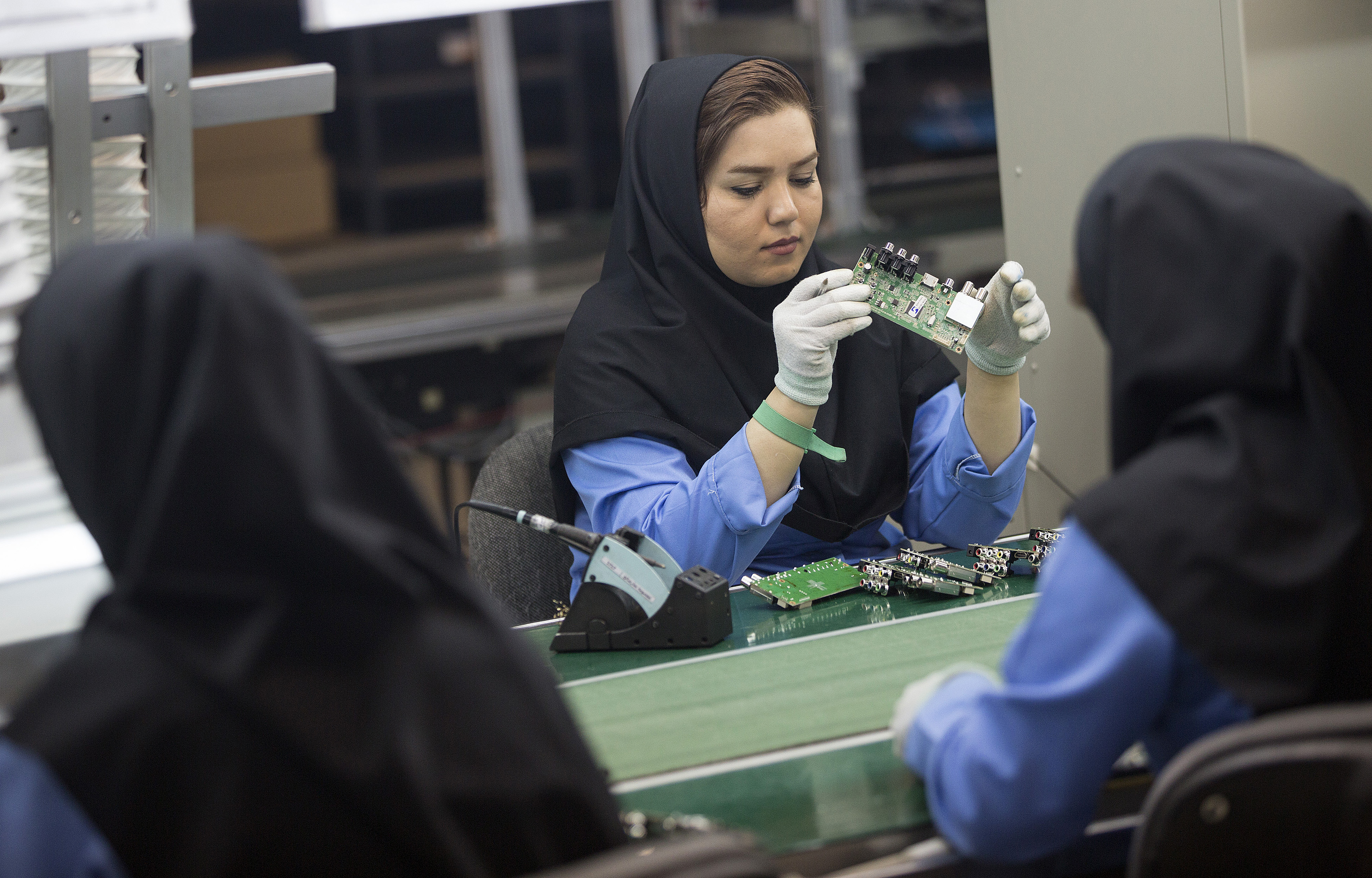 Female employees work on the assembly of electronic circuit boards at the Maadiran Group electronics distribution and manufacturing plant in Hashtgerd, Iran, on Tuesday, Sept. 1, 2015.
