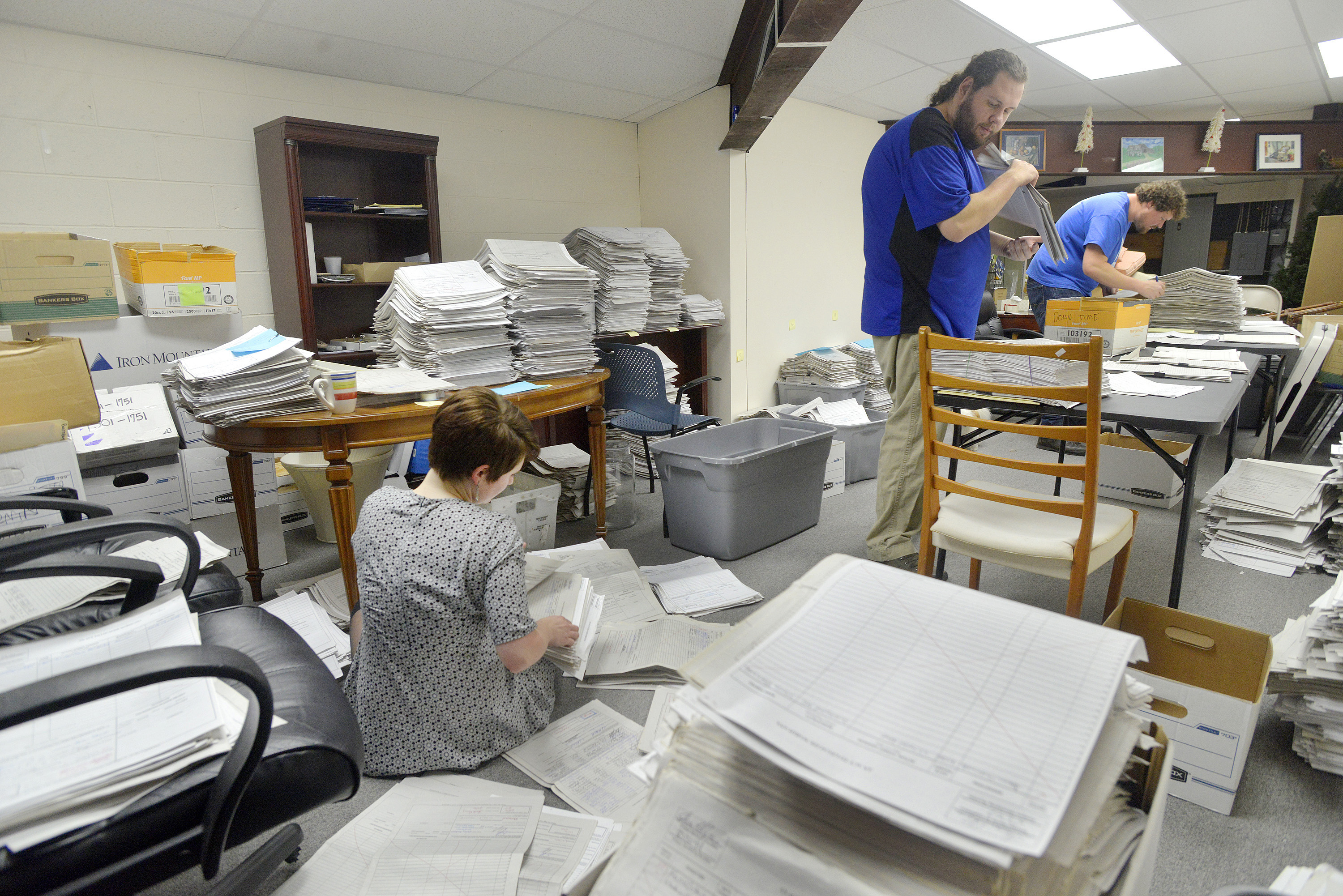 Staff and volunteers  for the marijuana legalization campaign are sorting petitions at their office in Falmouth. Volunteer Allison Cormier (left) along with office manager Shaun Bowen (center) and field director Jordan DeCoster sort and organize stacks of petitions at their campaign headquarters.