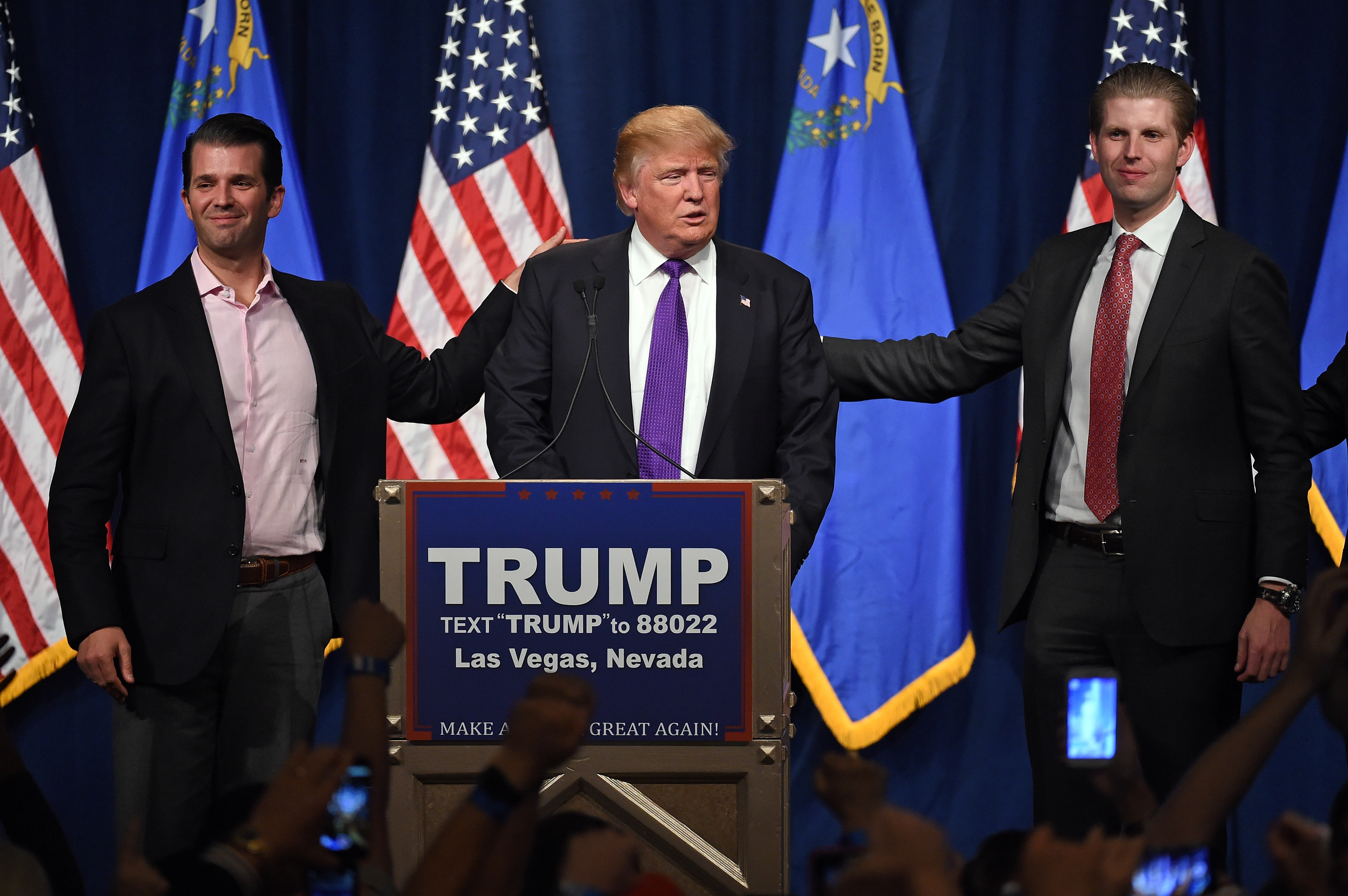 Republican presidential candidate Donald Trump (C) speaks as his sons Donald Trump Jr. (L) and Eric Trump (R) look on during a caucus night watch party at the Treasure Island Hotel & Casino on February 23, 2016 in Las Vegas, Nevada. The New York businessman won his third state victory in a row in the  first in the West  caucuses.