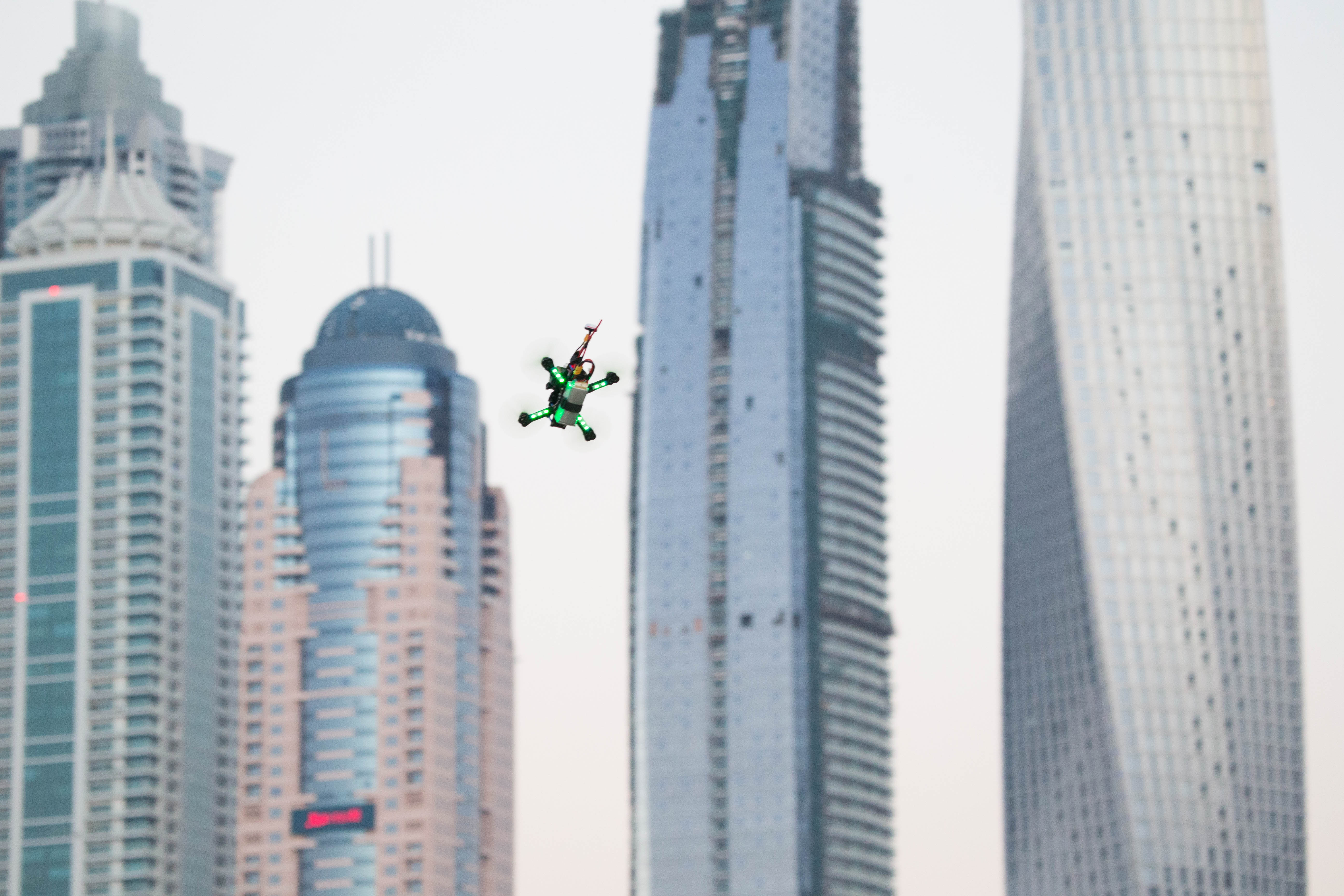 A drone flies around the track in front of the Dubai's Marina skyline during the World Drone Prix drone racing championship in Dubai, United Arab Emirates, on Saturday, March 12, 2016. Teams compete for the global champion purse of total prizes of $1 million by navigating drones at over 100kms an hour around a track which features multiple pathways, kinetic and static obstacles designed to push pilots to their limits.