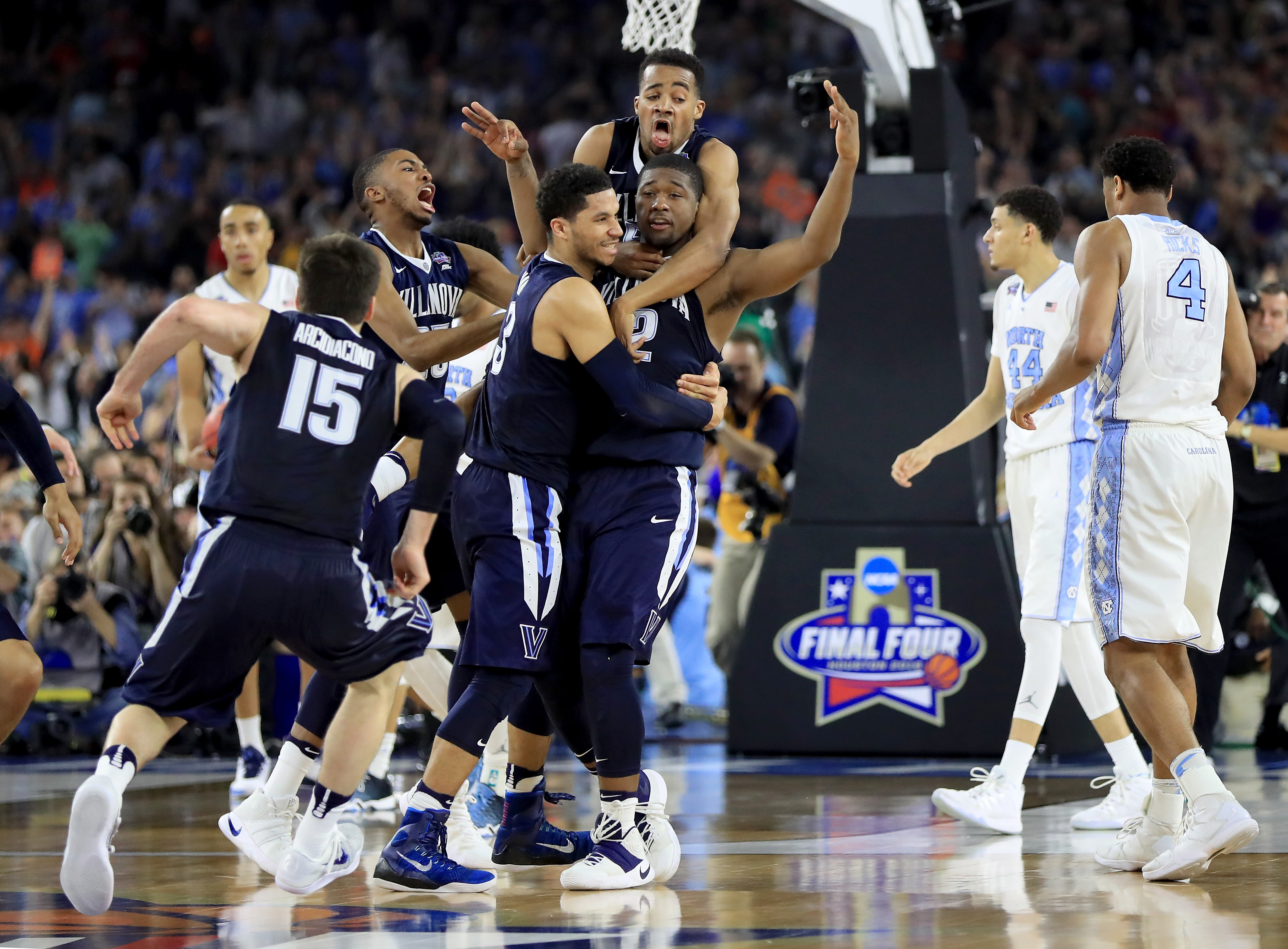 Villanova players mob teammate Kris Jenkins (#2) after he sinks a buzzer-beater to beat North Carolina in the national championship game at NRG Stadium in Houston, Texas on April 4, 2016