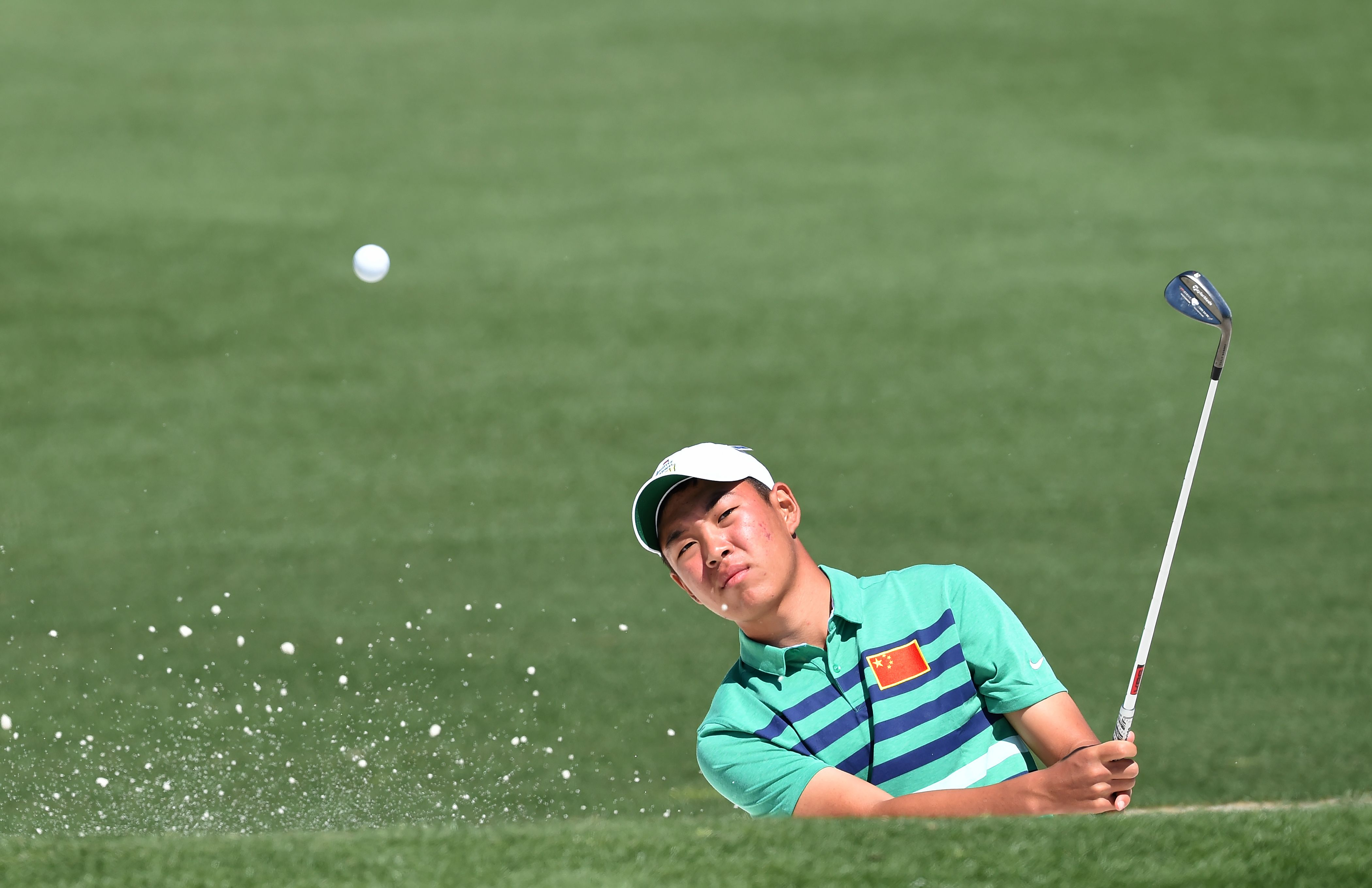 China's Jin Cheng hits out of a bunker during a practice round prior to the start of the 80th Masters Golf Tournament at the Augusta National Golf Club in Augusta, Ga., on April 5, 2016