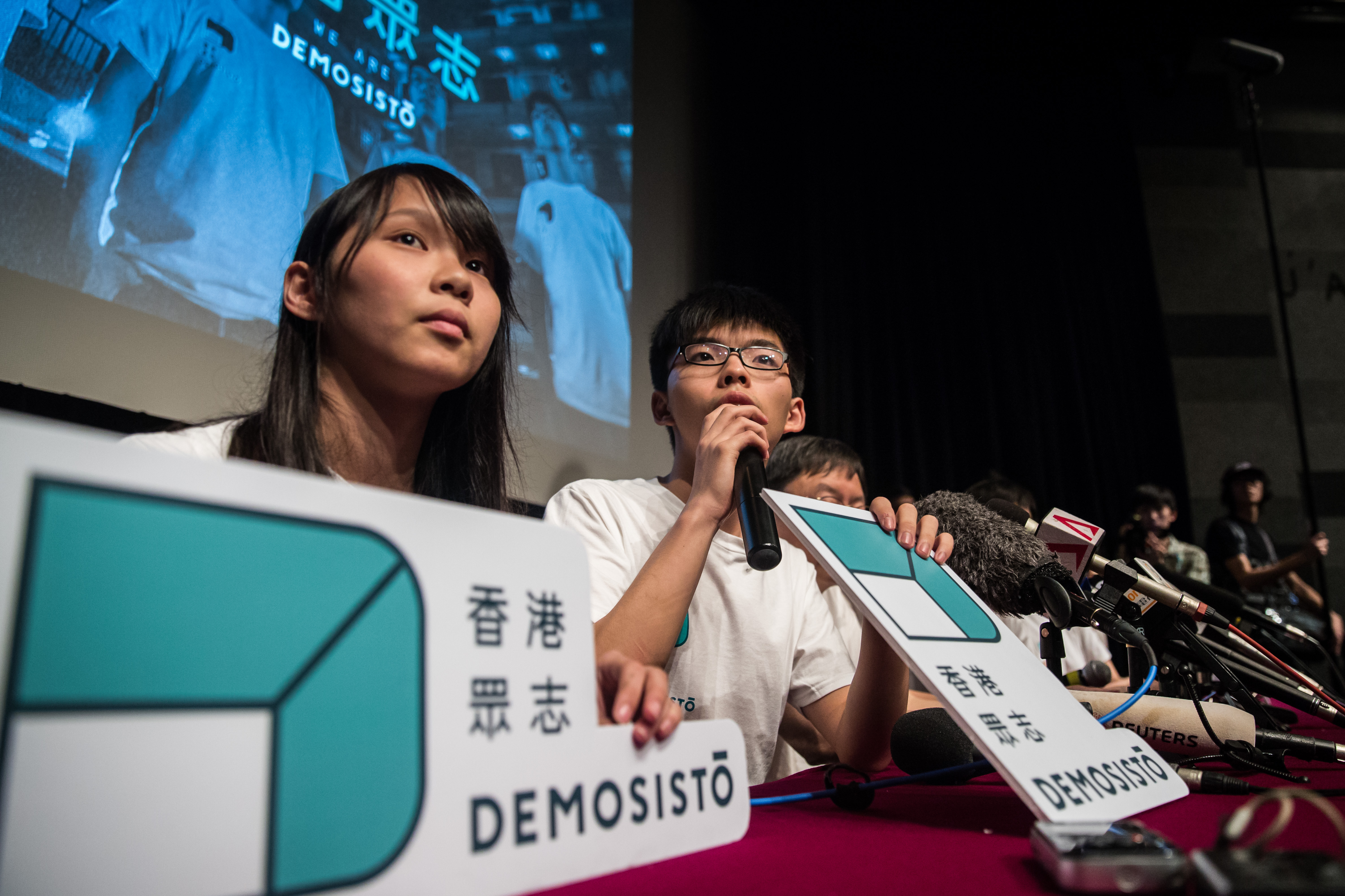 Pro-democracy student leader Joshua Wong, center, speaks as Agnes Chow listens during a press conference to introduce their new pro-democracy political party called Demosistō in Hong Kong on April 10, 2016