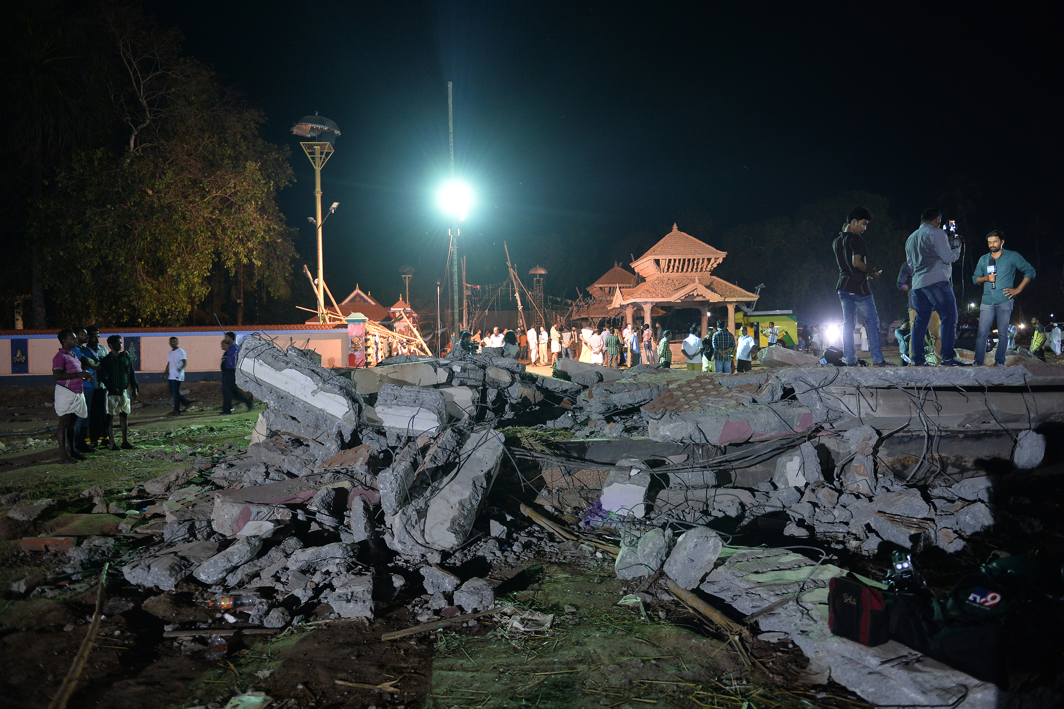 Onlookers stand amid the debris in the aftermath of the deadly fire explosion that rocked Puttingal Temple in Paravoor, nearly 40 miles (60 km) northwest of Thiruvananthapuram in Kerala state, India, on April 10, 2016