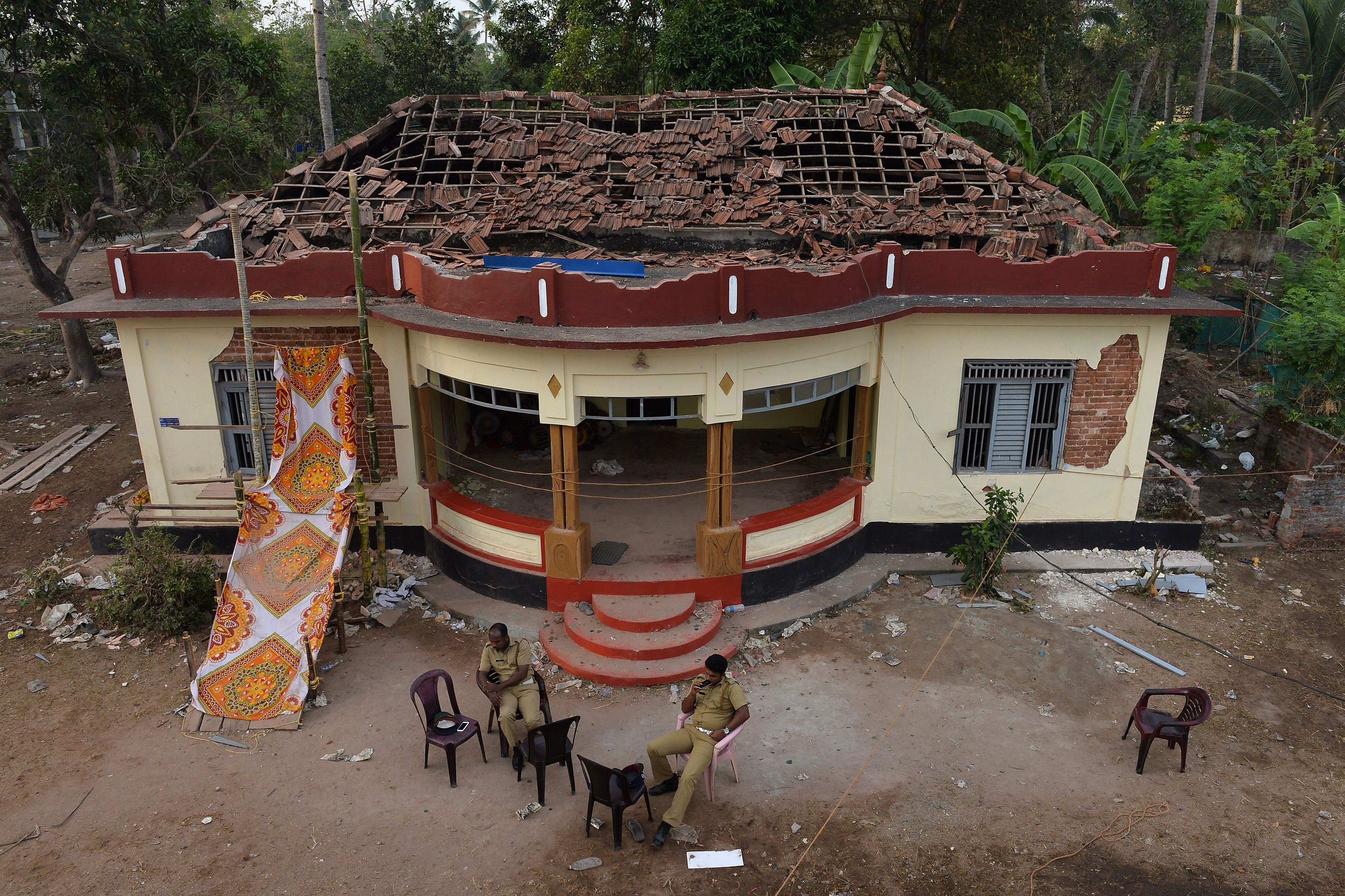 Indian police personnel sit in front of a damaged building at Puttingal Temple in the Indian town of Paravoor, some 60 km northwest of Thiruvananthapuram, Kerala state, on April 11, 2016