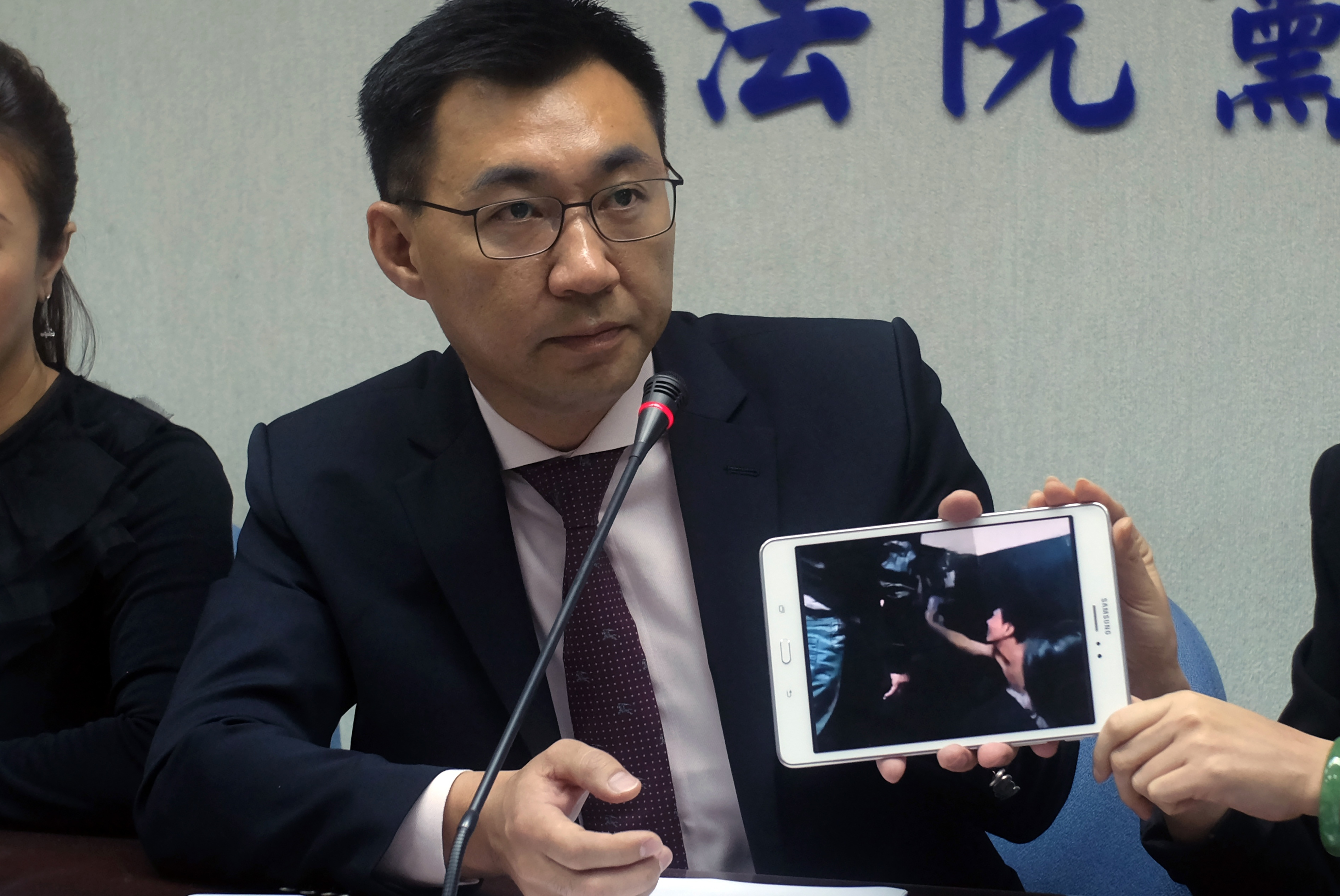 Johnny Chiang, a legislator from the Kuomintang  party, displays a video clip showing Taiwanese detained at a police station in Kenya, during a press conference in Taipei on April 12, 2016