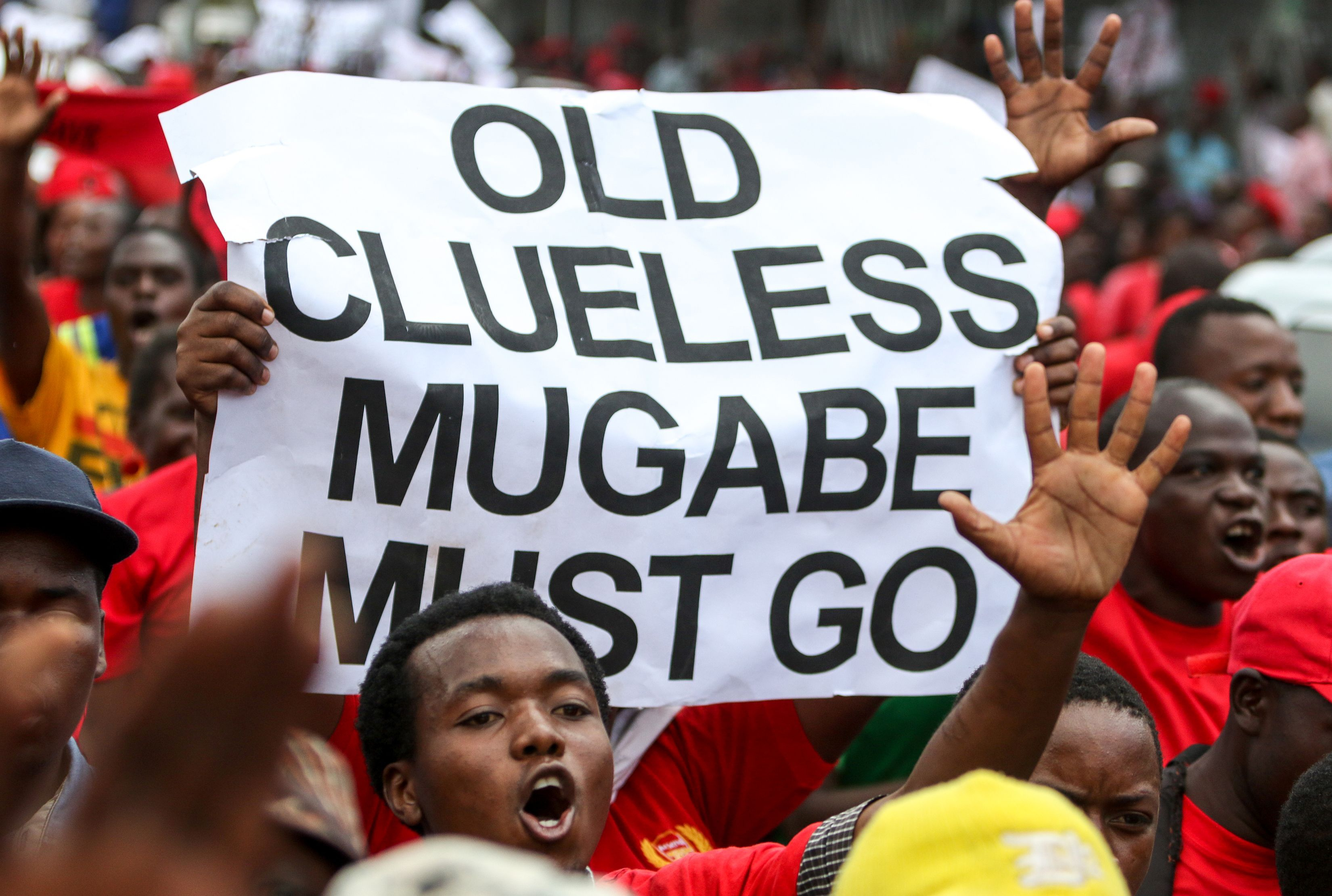 Movement for Democratic Change (MDC) youth supporters hold up a sign during a demonstration by the opposition party in Harare on April 14, 2016