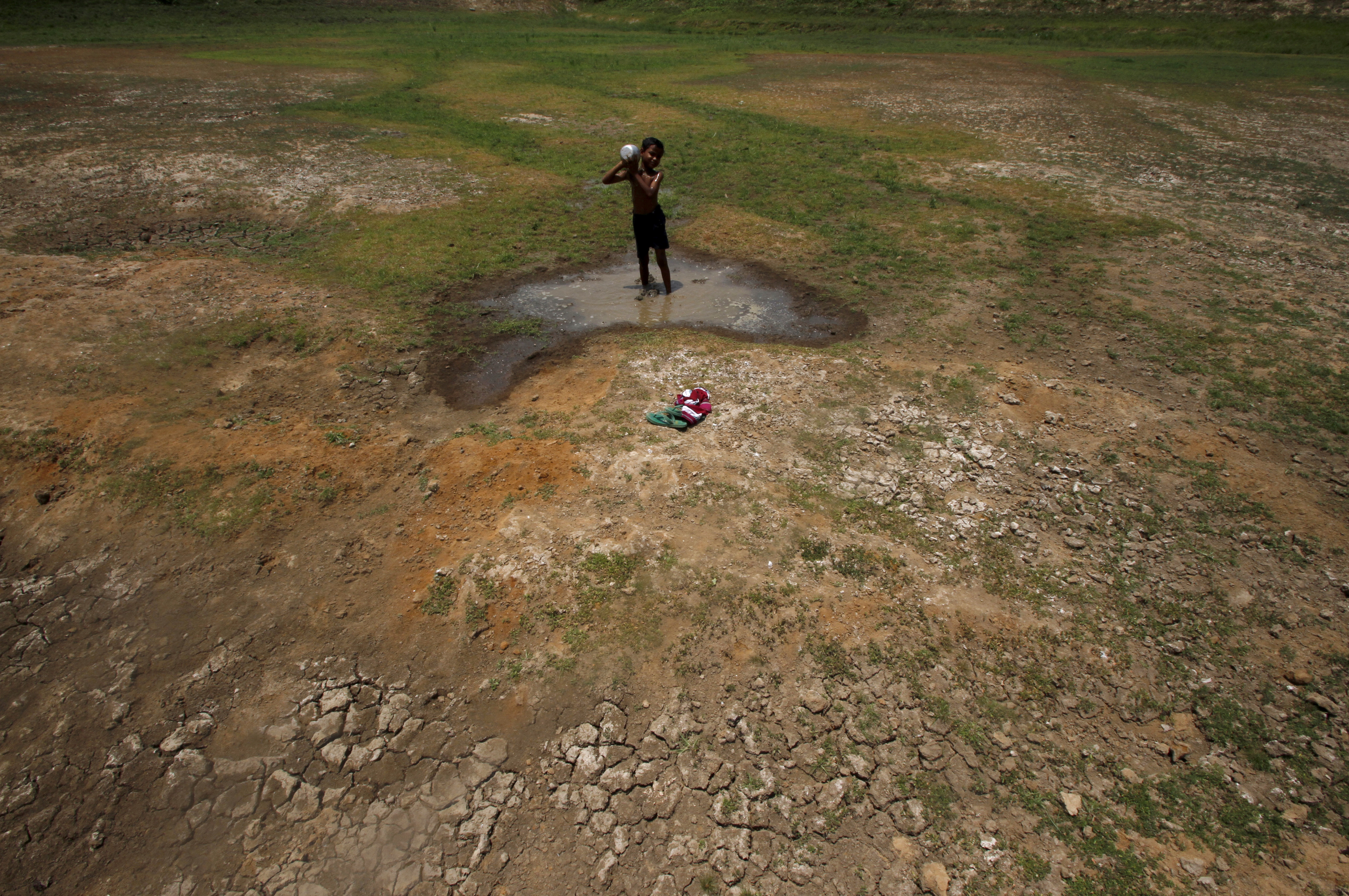 A village boy baths in the remaining water of a dried pond to beat the heat in the outskirts of the eastern Indian city of Bhubaneswar on April 23, 2016