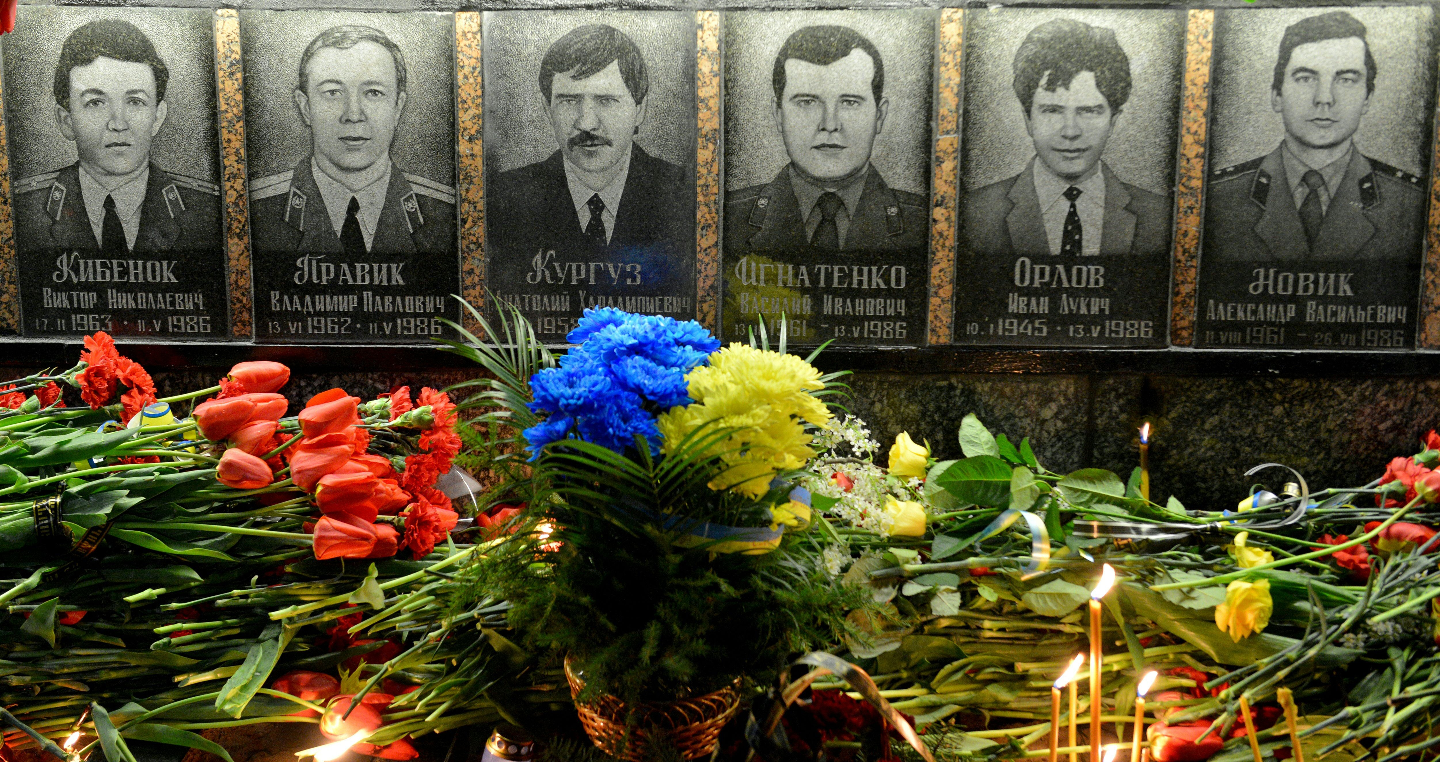Picture taken early on April 26, 2016 shows flowers and candles in front of portraits at the monument to Chernobyl victims in Slavutich, some 50 kilometres (30 miles) from the accident site, and where many of the power station's personnel used to live, during a memorial ceremony.