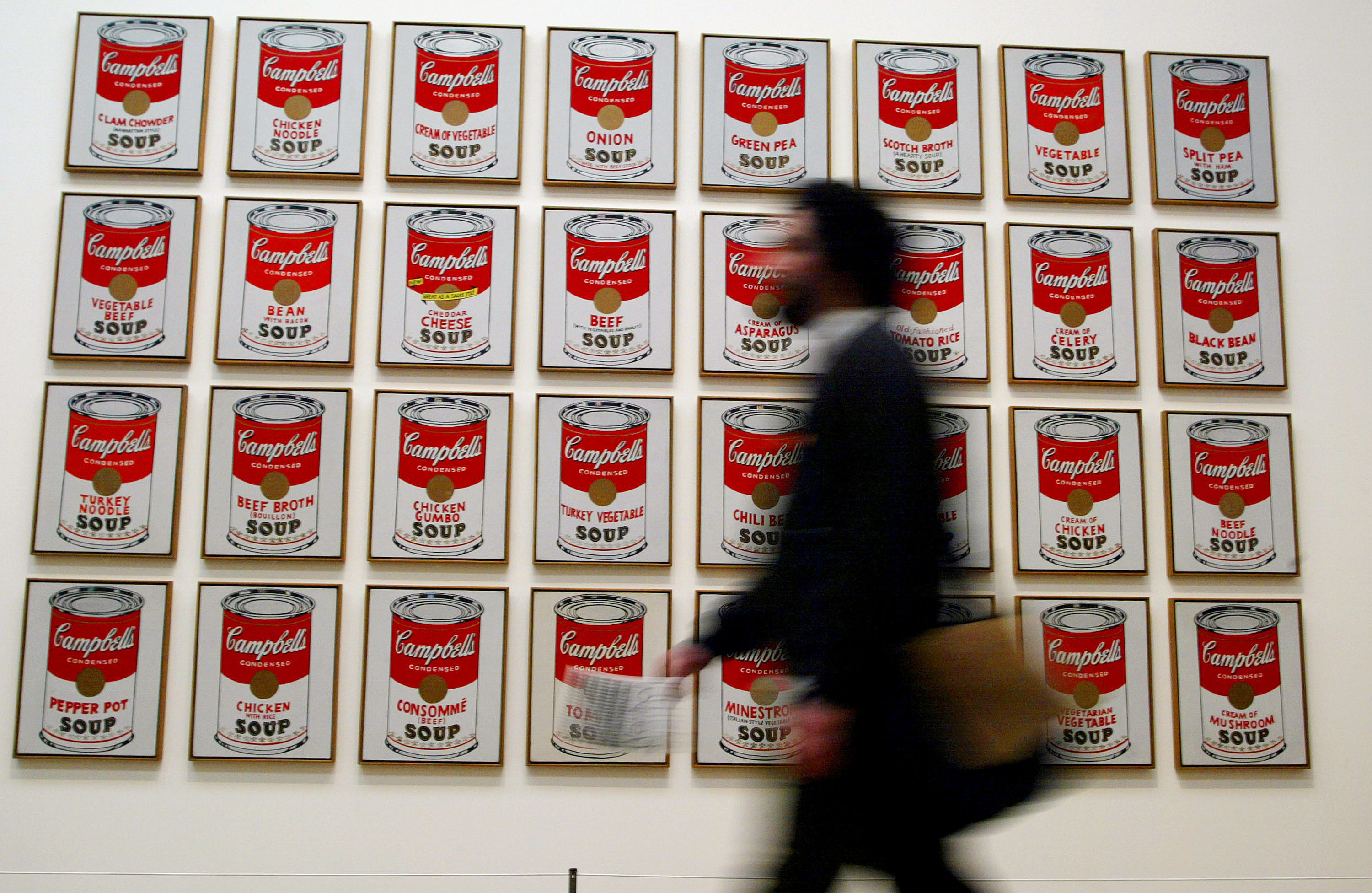 A spectator walks past  Campbells Soup Cans  created in 1962 by artist Andy Warhol at the Andy Warhol retrospective exhibition February 5, 2002 at the Tate Modern Gallery in London.
