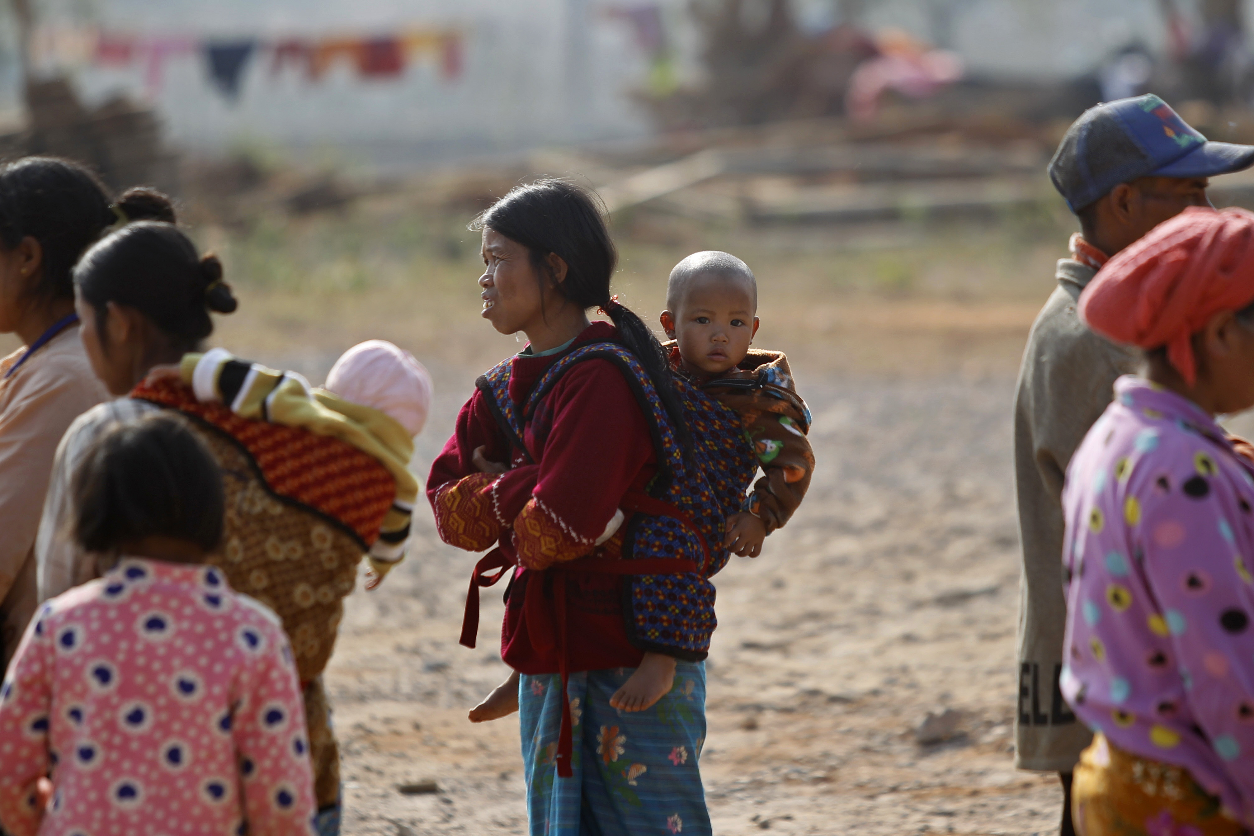 A woman carries her child on her back outside a monastery that has been set up as temporary refugee camp in Kyaukme, in Burma's northern Shan state, on Feb. 21, 2016