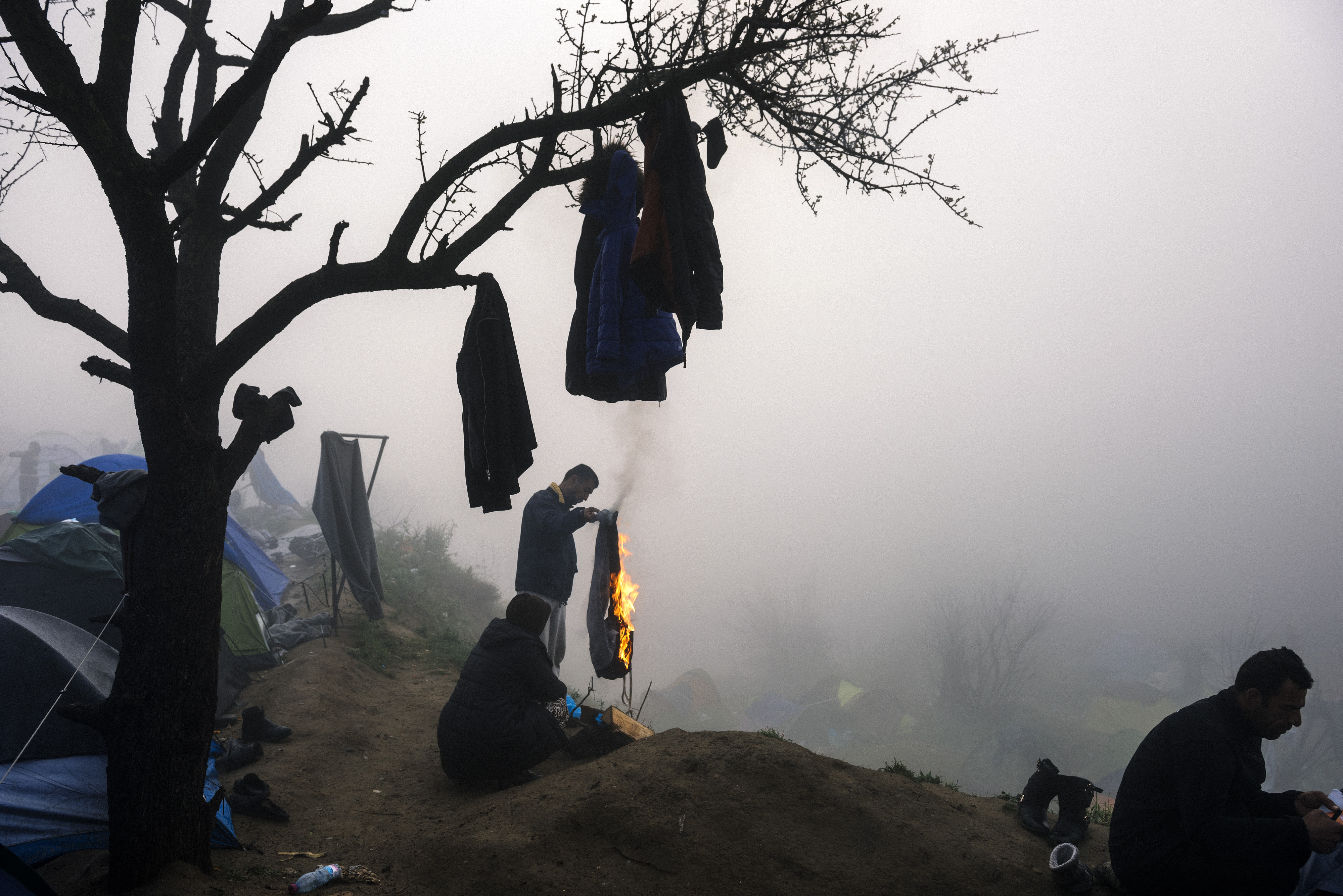 A man burns a pair of trousers to make it a bonfire during a foggy morning at a makeshift camp at the Greek-Macedonian border near the Greek village of Idomeni where thousands of refugees and migrants are stranded on March 8, 2016.