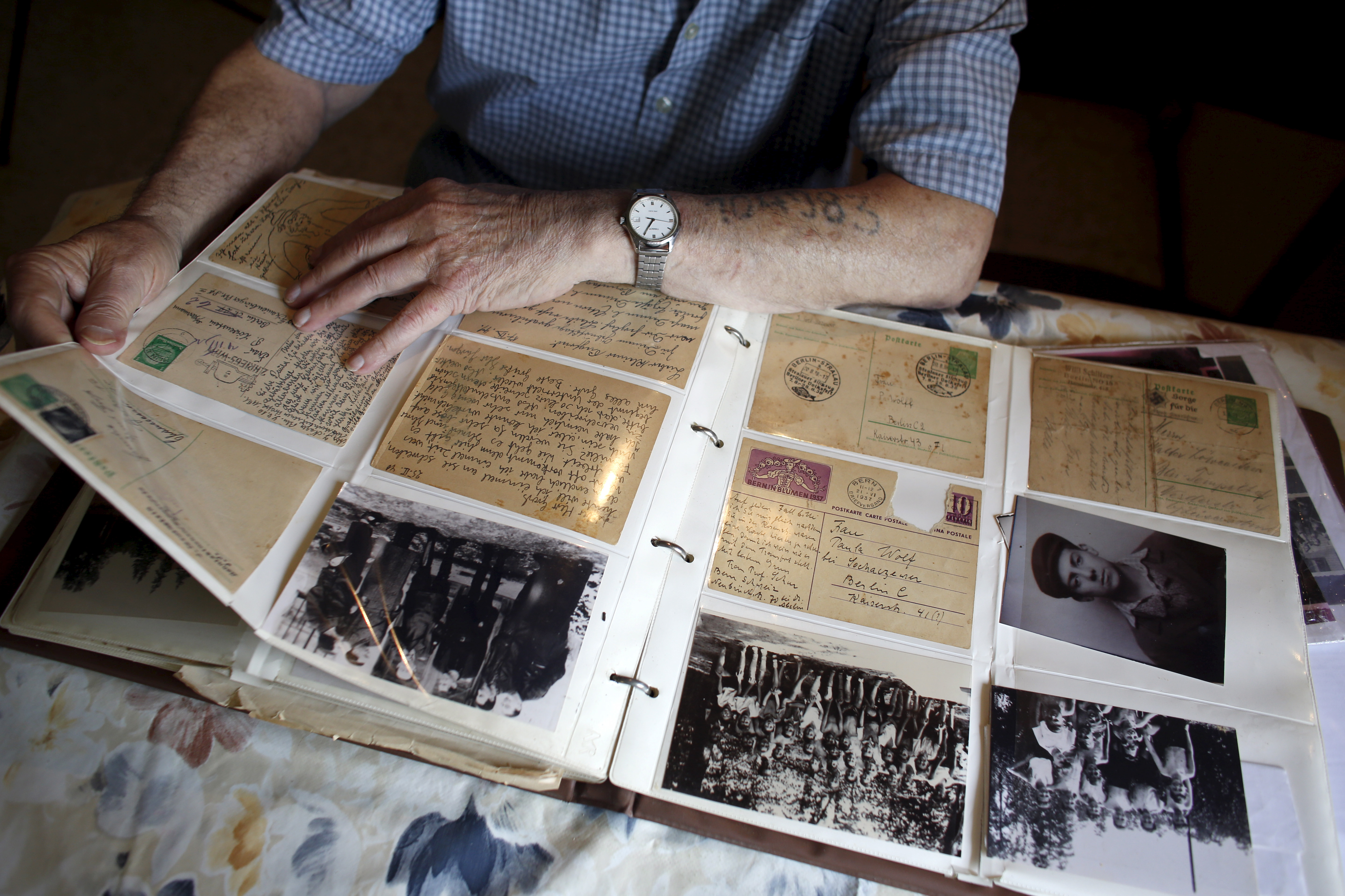 Holocaust survivor Israel Loewenstein, 91, looks at a photo album at his home in Yad Hana, Israel on April 6, 2016.