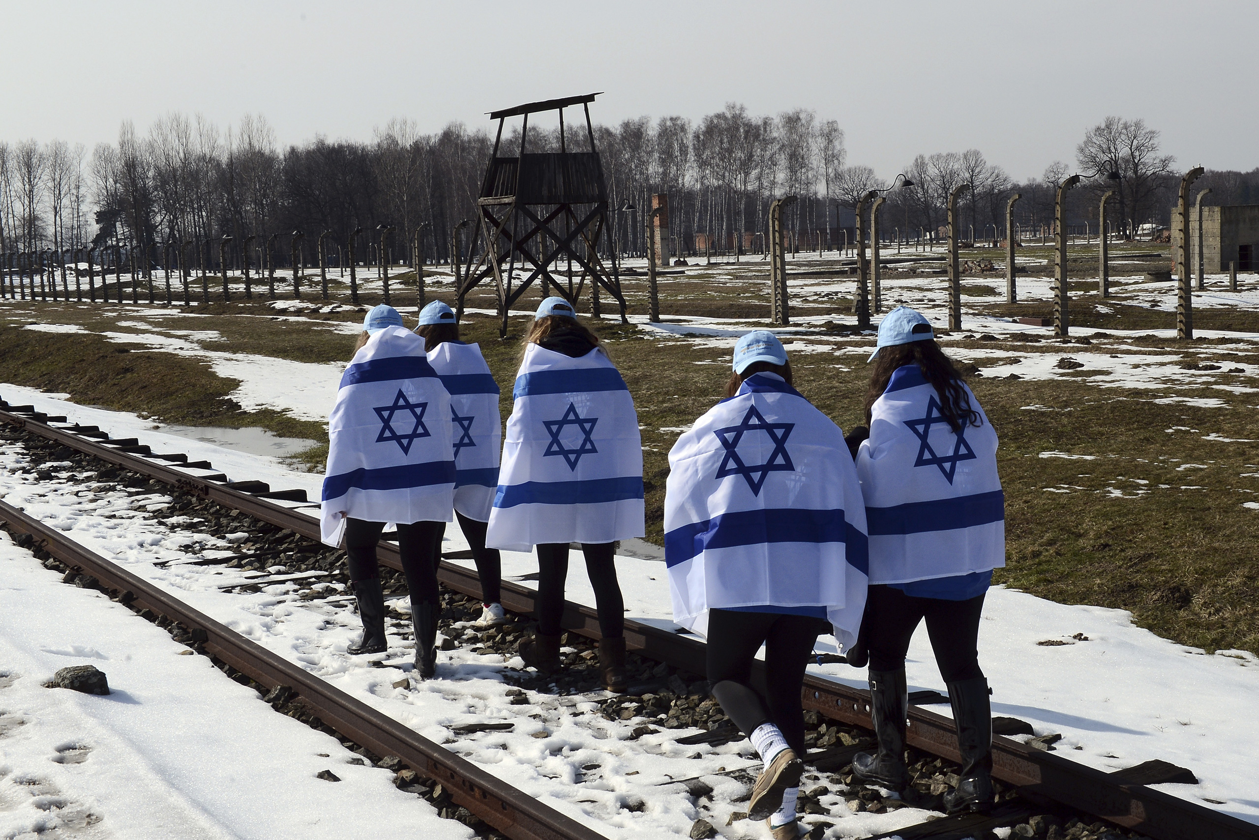 Participants of the annual  March of the Living  carry the Israeli flag wrapped around their shoulders as they walk along the rail road of the Auschwitz-Birkenau concentration camp in Oswiecim, Poland, April 8, 2013.