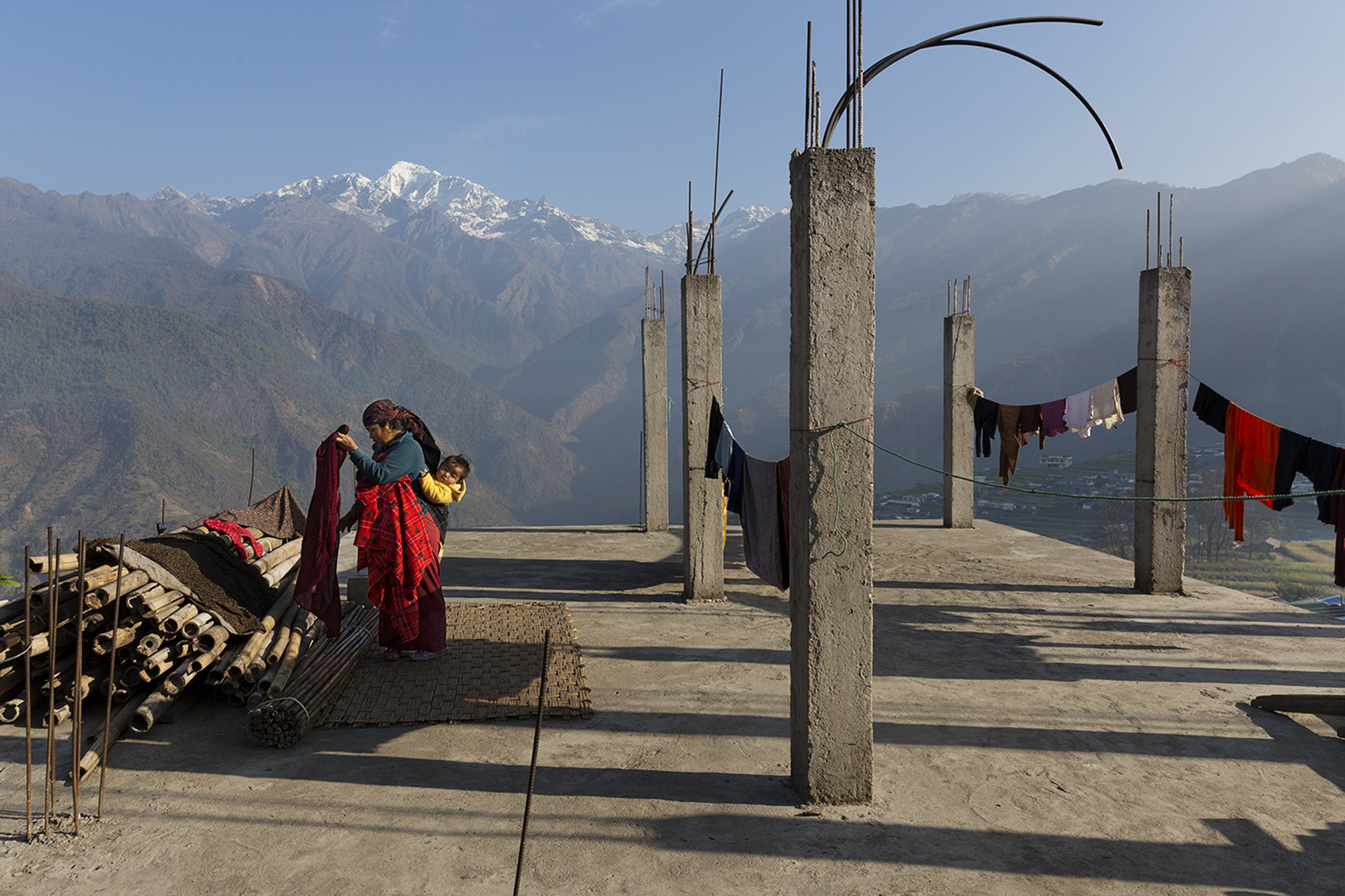 A woman hangs laundry with the Buddha Himal mountain behind her in the Himalyan village of Barpak, in Gorkha district, Nepal. Though international donors stepped up to provide aid in the aftermath of the 2015 quakes, money for rebuilding homes has yet to reach victims. April 6, 2016.