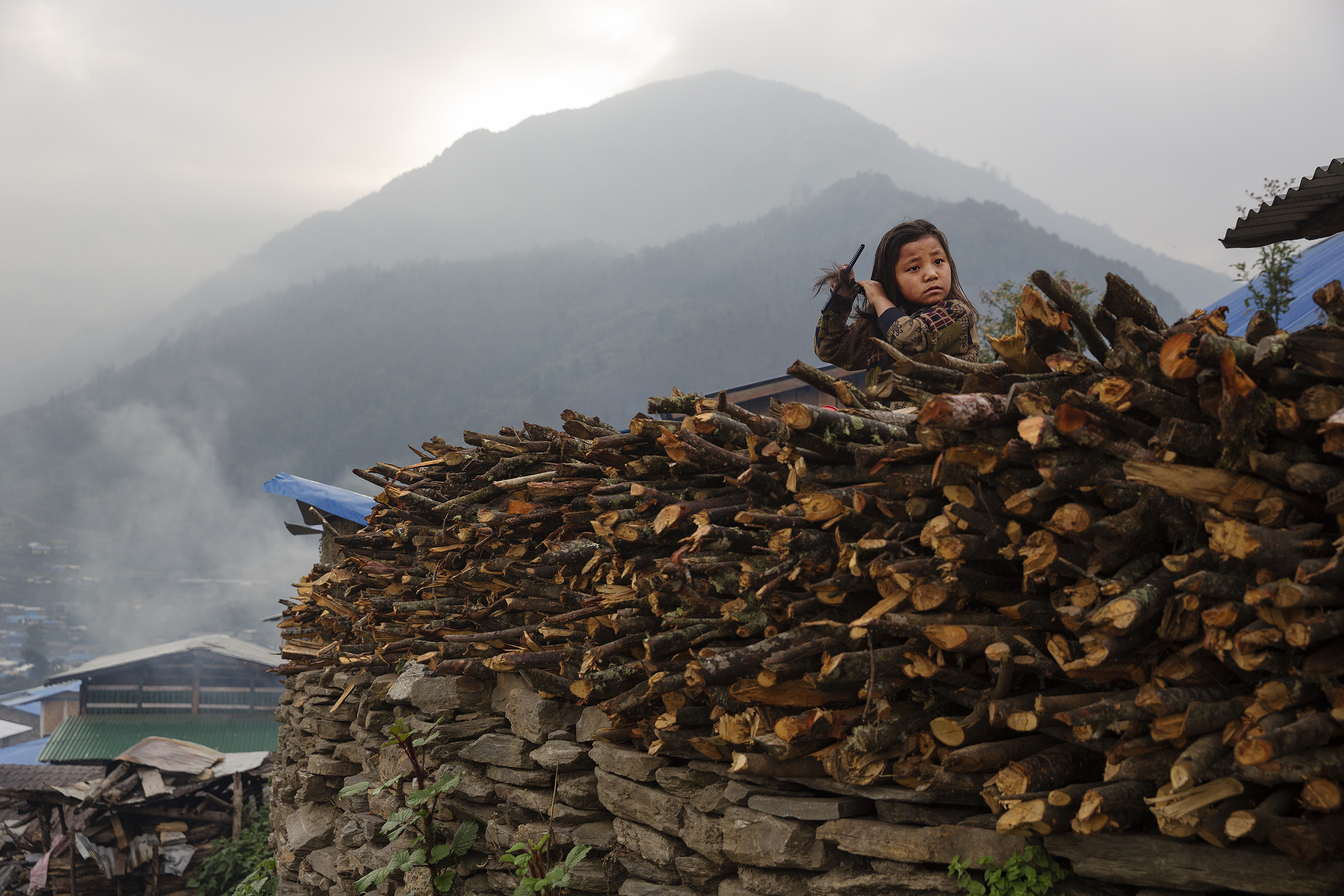 A child combs her hair in the devastated village of Barpak, in Gorkha district, Nepal, a year after the 2015 quakes which destroyed most of the town, April 5, 2016.