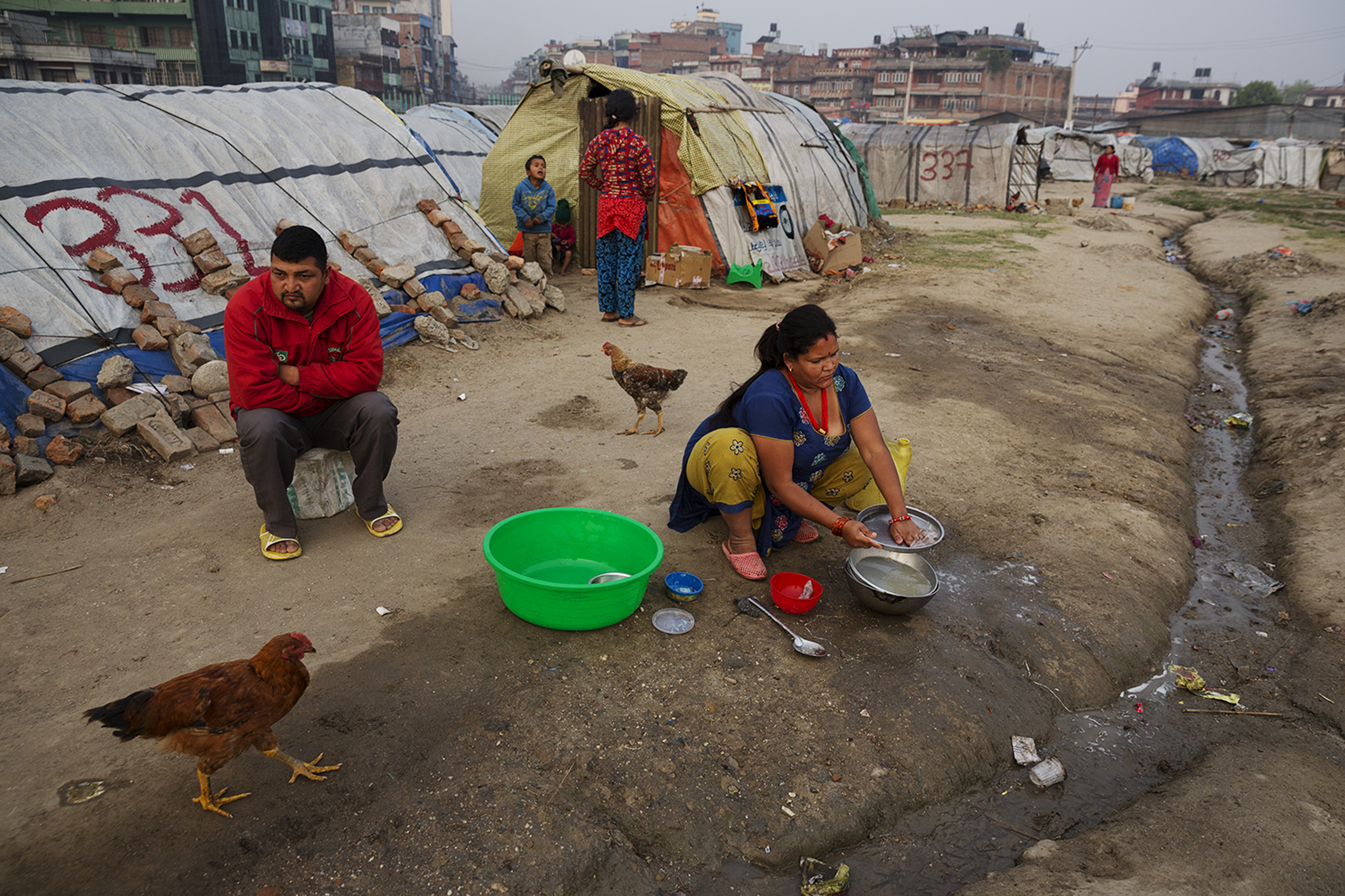 A family sits in an Informal tent encampment in central Kathmandu, Nepal. Approaching the first anniversary of the  quakes of 2015, many people have been living in the squalid conditions of the camp for the past year.  Some residents of the camp are from towns and villages in the region of Kathmandu, while others, some of whom are Nepalese migrant workers, are from more distant areas, March 31, 2016.