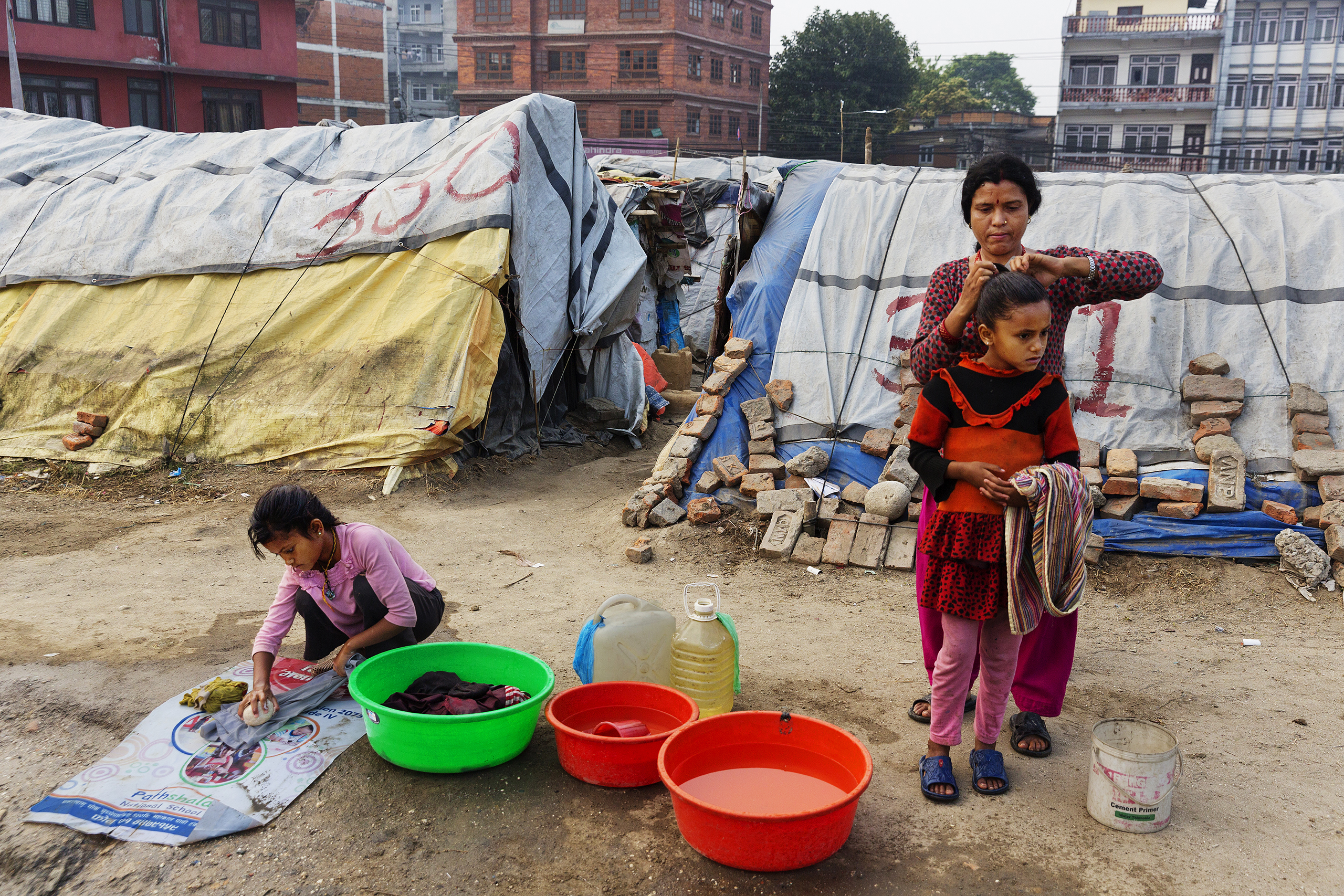 A woman and children at a squalid  tent encampment in central Kathmandu, Nepal, nearly a year after the devastating 2015 earthquakes, March 31, 2016.