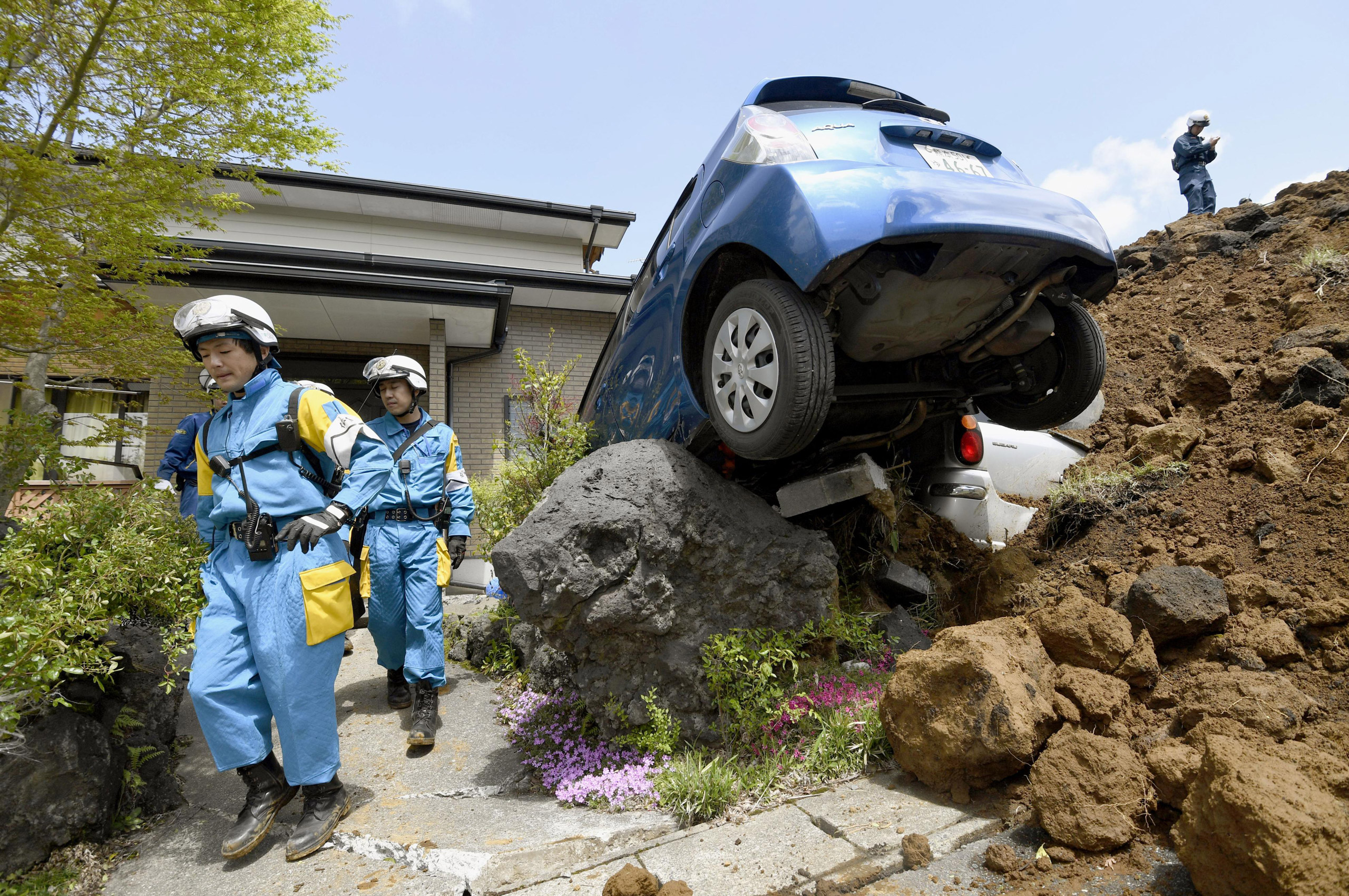 Police officers conduct a search operation at the site of a landslide caused by an earthquake in Minamiaso, Japan, on April 17, 2016.