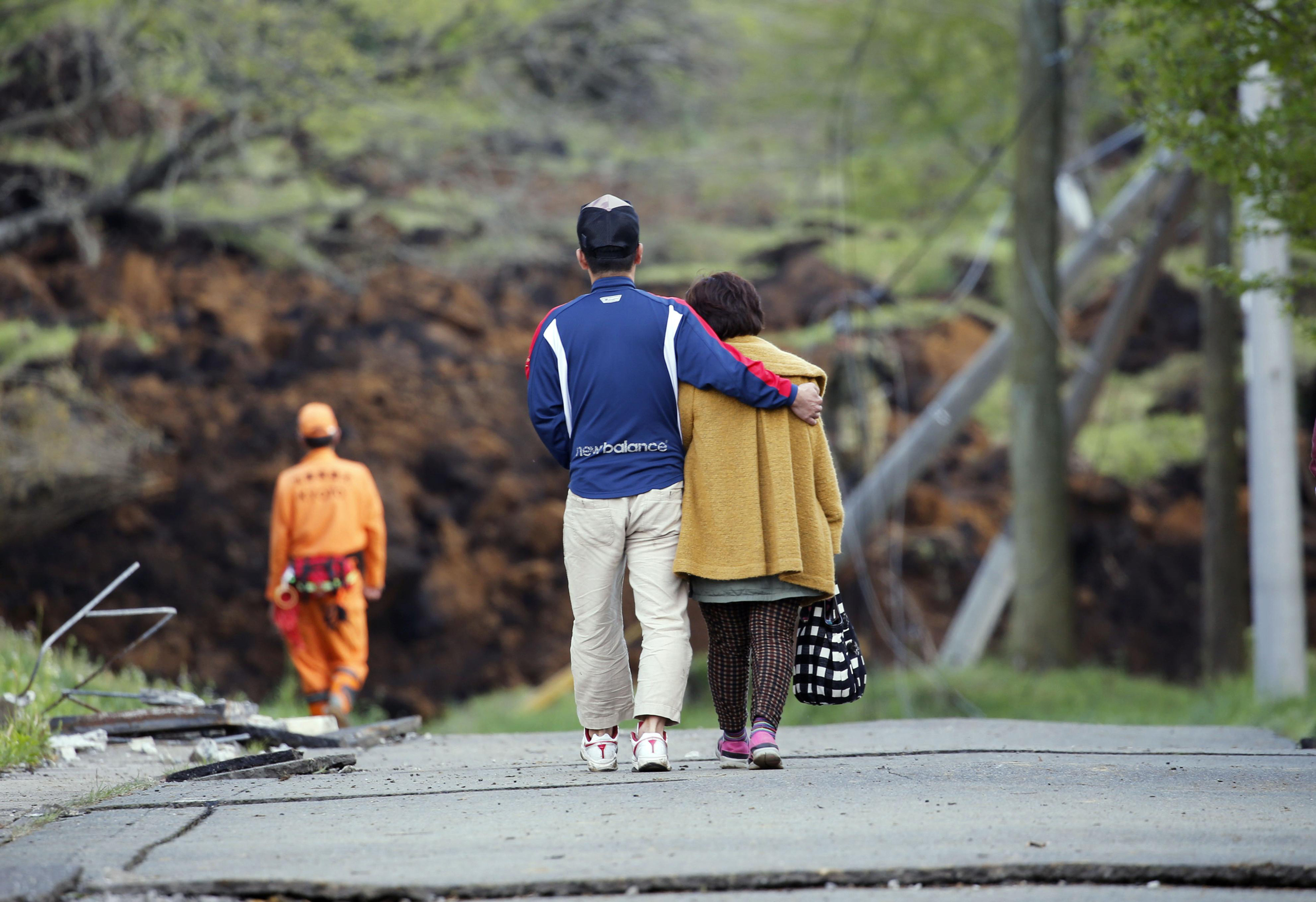 A man hugs his mother as they leave their house buried in a landslide caused by earthquakes in Minamiaso, Japan, on April 17, 2016.