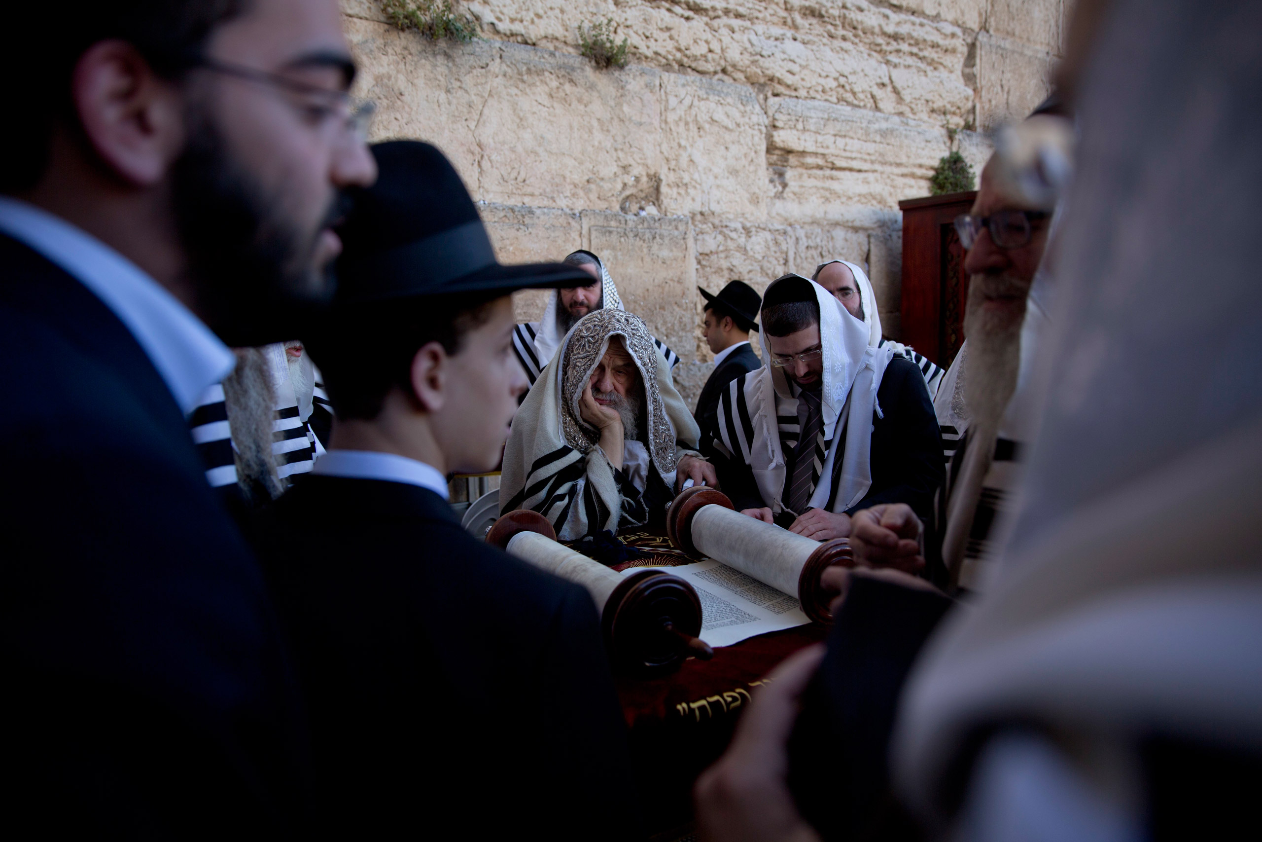 Covered in prayer shawls, ultra-Orthodox Jewish men read from a Thora scroll during the Jewish holiday of Passover in front of the Western Wall, the holiest site where Jews can pray, in Jerusalem's Old City on April 24, 2016.