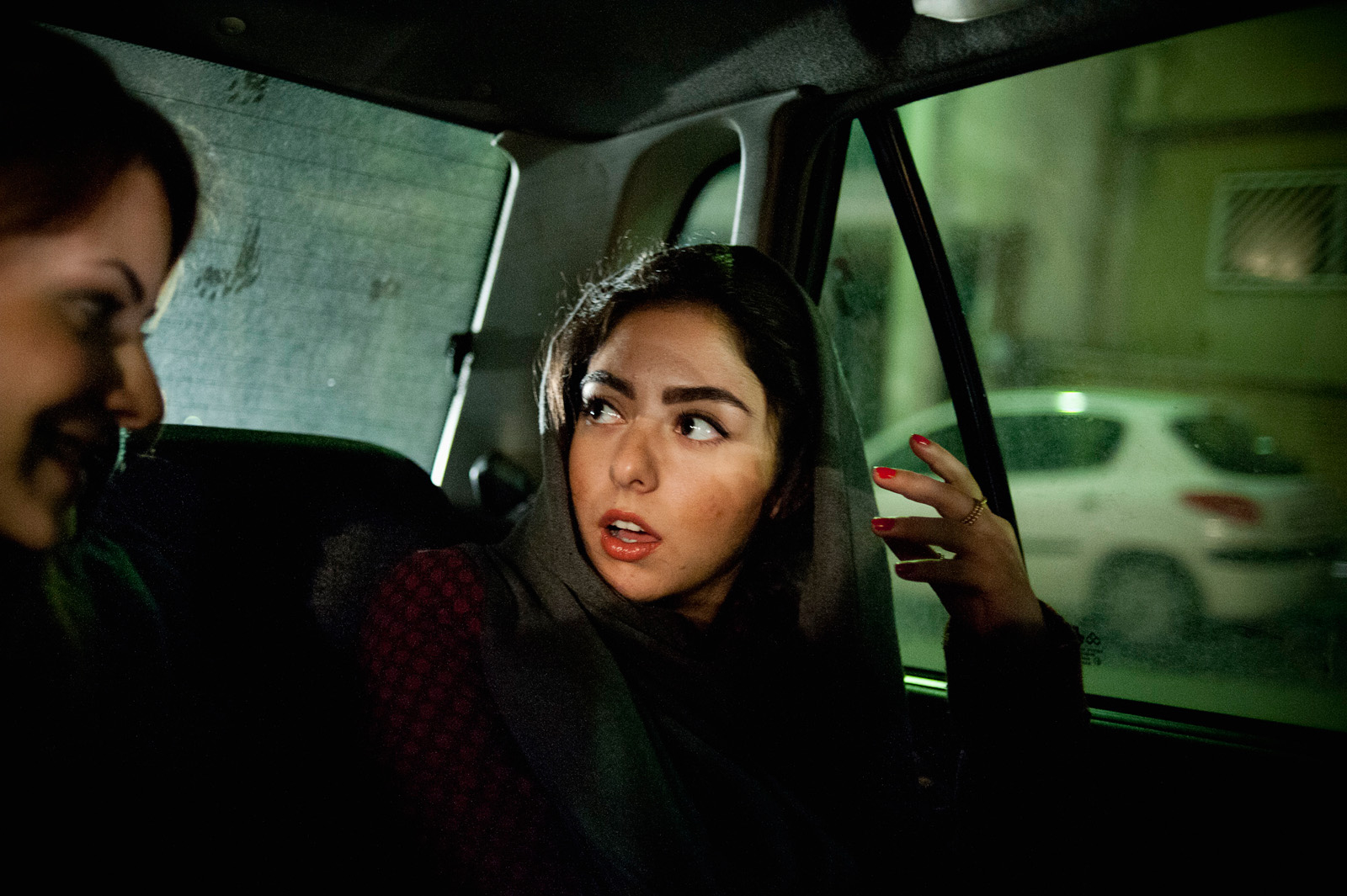 Yassi and her friend take a cab to an opening reception at a gallery in northern Tehran. Even though being bold and eye-catching is always a factor that concerns the morality police, many girls choose to put on bright lipstick and wear distinctive fashion. Tehran, Iran, Nov. 24, 2011.