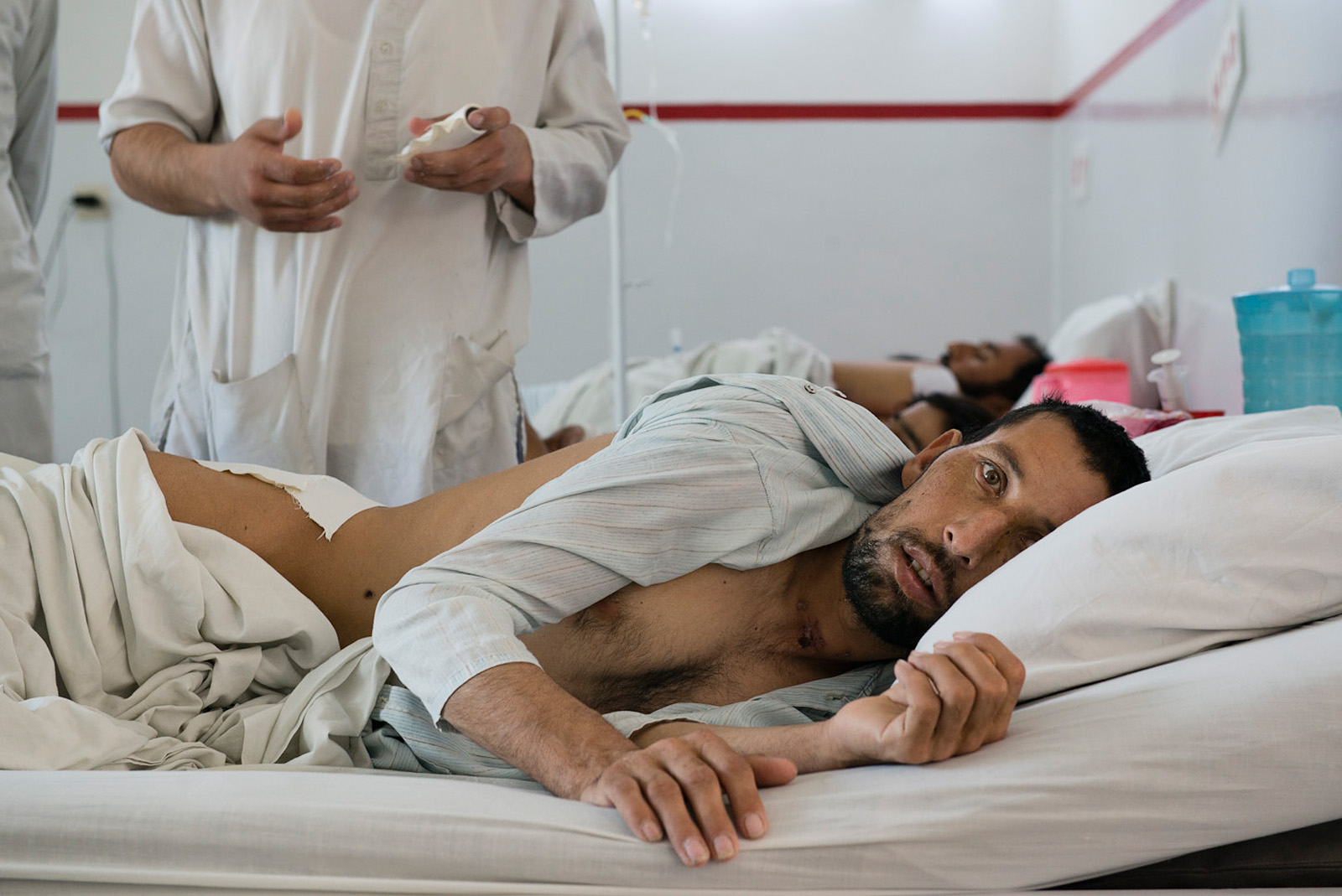 A 23 year old police officer, unable to speak from a severe injury to his jaw caused by shrapnel during the fighting against Taliban, lays in his bed at the Italian Emergency Hospital, while nurses treat his wounds on his back. Kabul, Afghanistan, May 25, 2015.