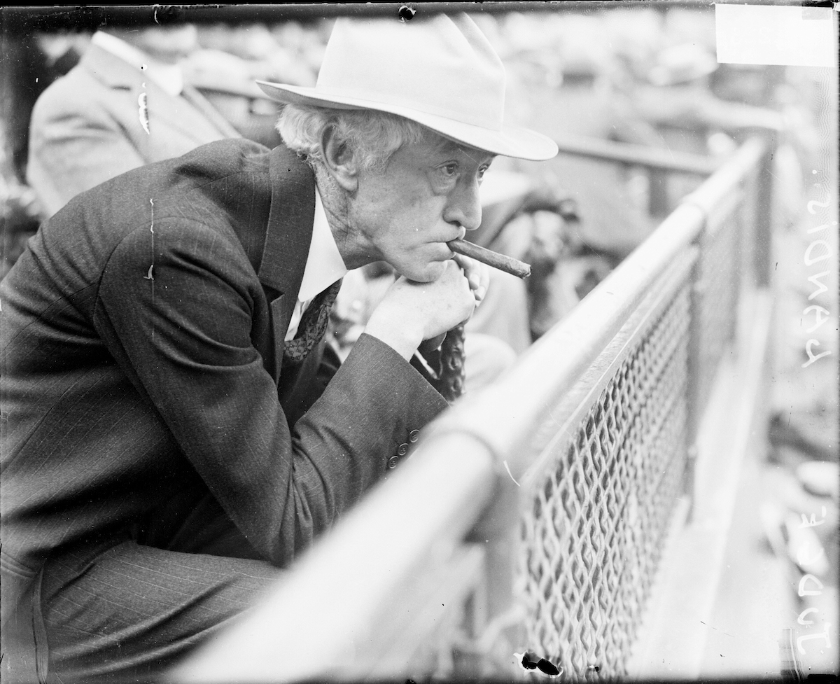 Judge Kenesaw Mountain Landis, commissioner of baseball from 1920-1944, sitting in profile in the stands at a baseball game in an outdoor stadium in Chicago, 1929.