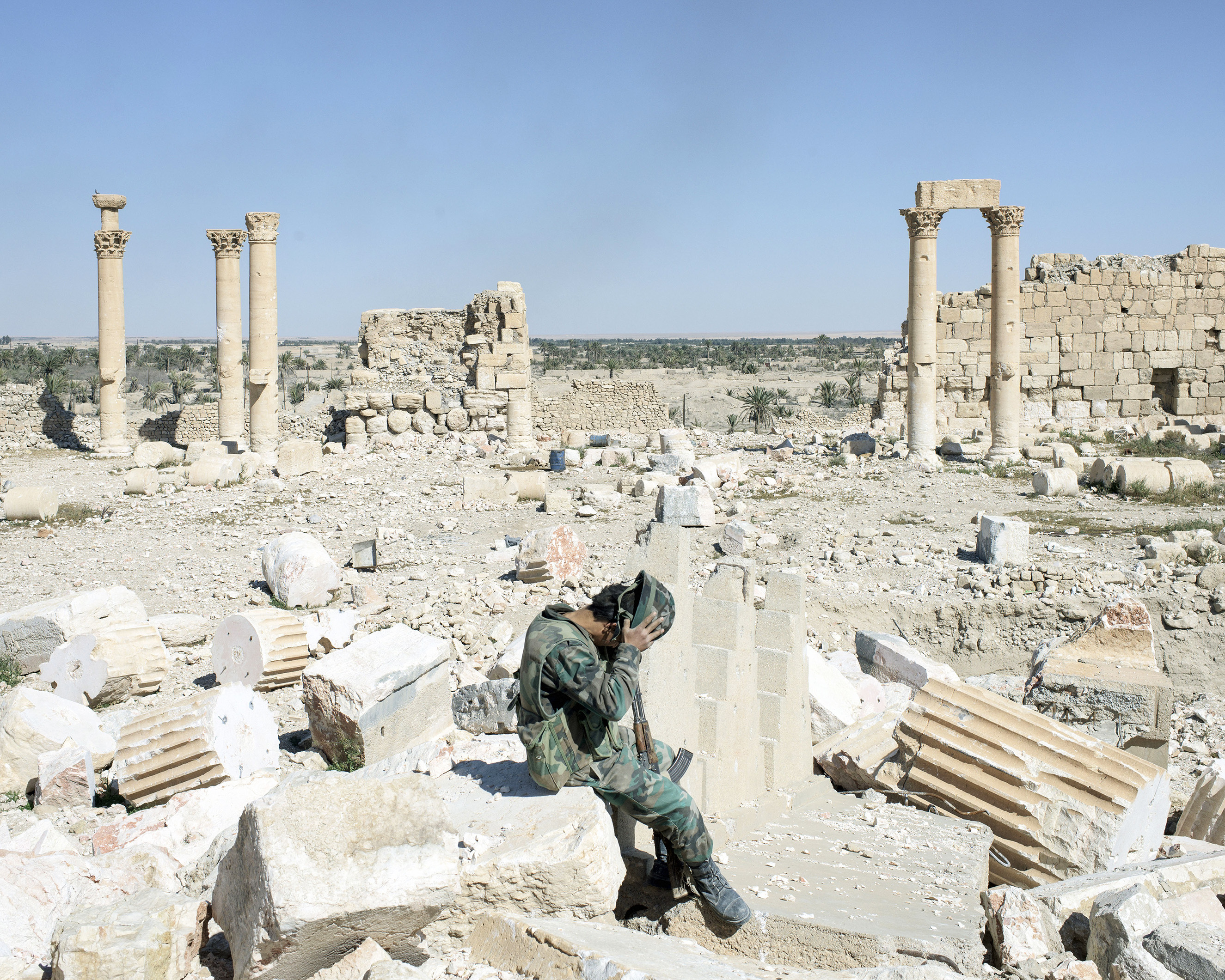 A Syrian army soldier removes his helmet while sitting on rubble of the former Temple of Bel, one of several sites destroyed by ISIS militants, in ancient Palmyra, Syria, April 1, 2016.From  Inside War Ravaged Syria