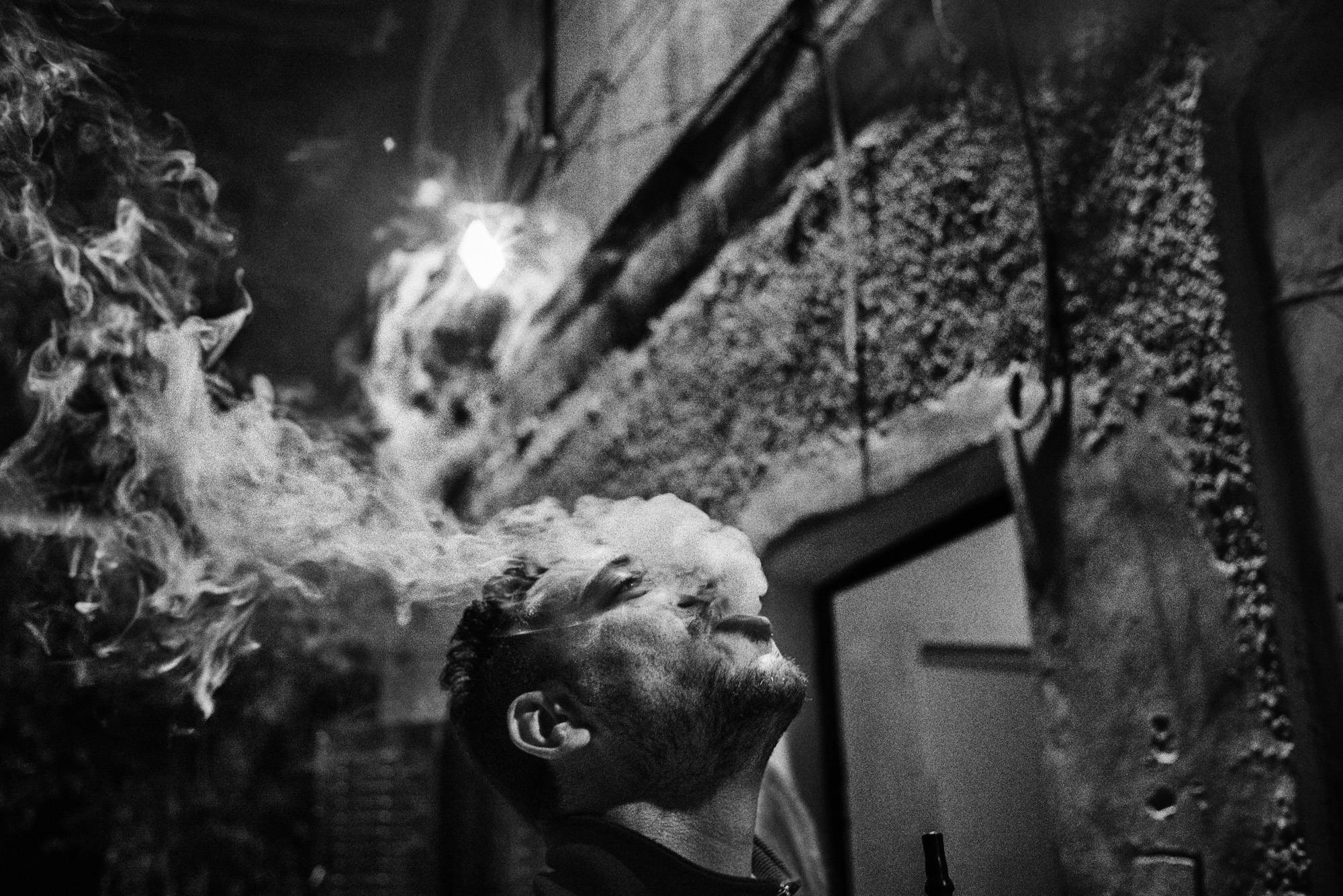 Muhannad Qafesha smokes shisha outside the headquarters of Youth Against Settlements, a Palestinian activist organization located in the Tel Rumeida neighborhood of Hebron, November 2015.