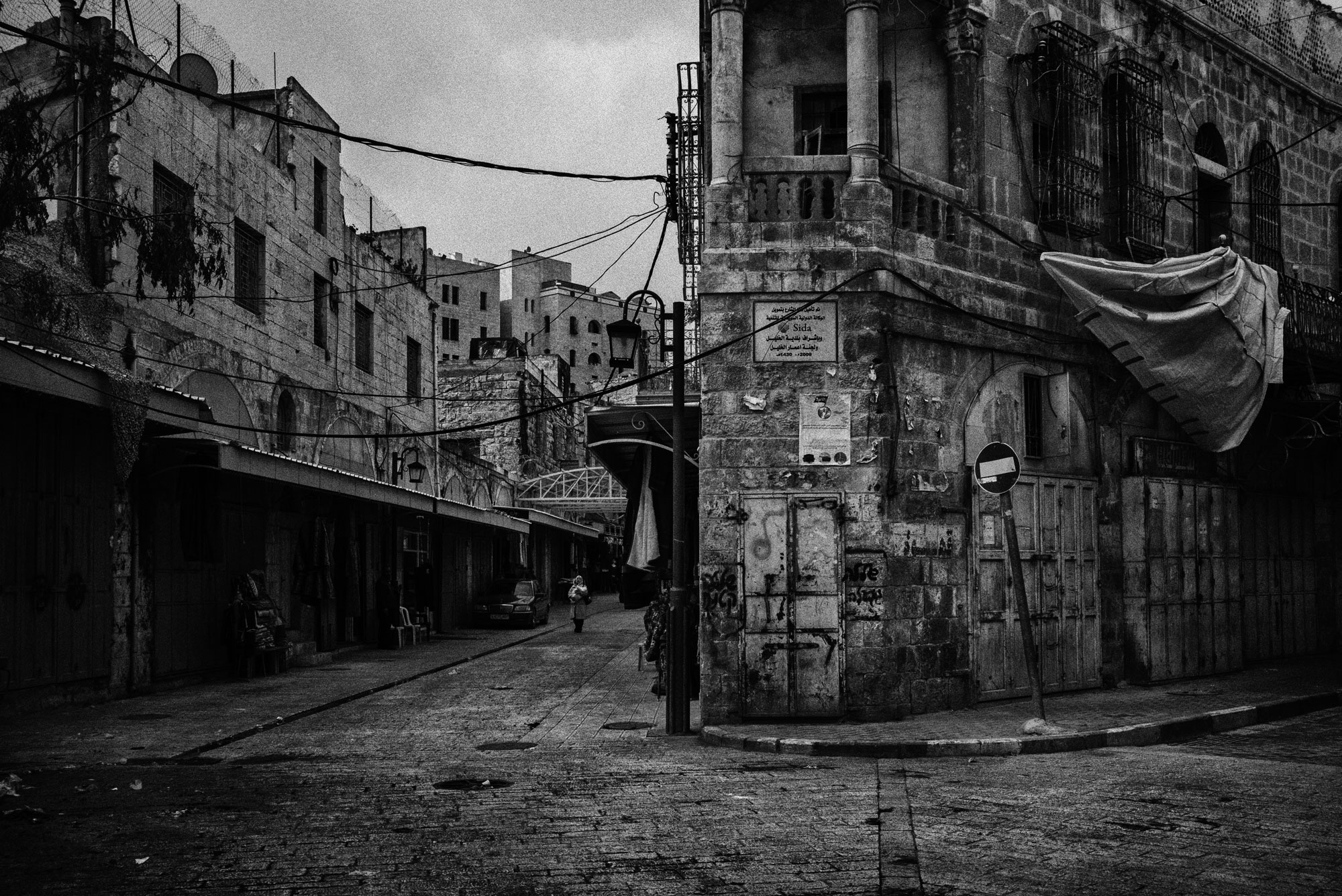 The homes of Jewish Israeli settlers can be seen on the left side of the road just over the closed shops in this area of Hebron's Old City, once a thriving market, November 2015.