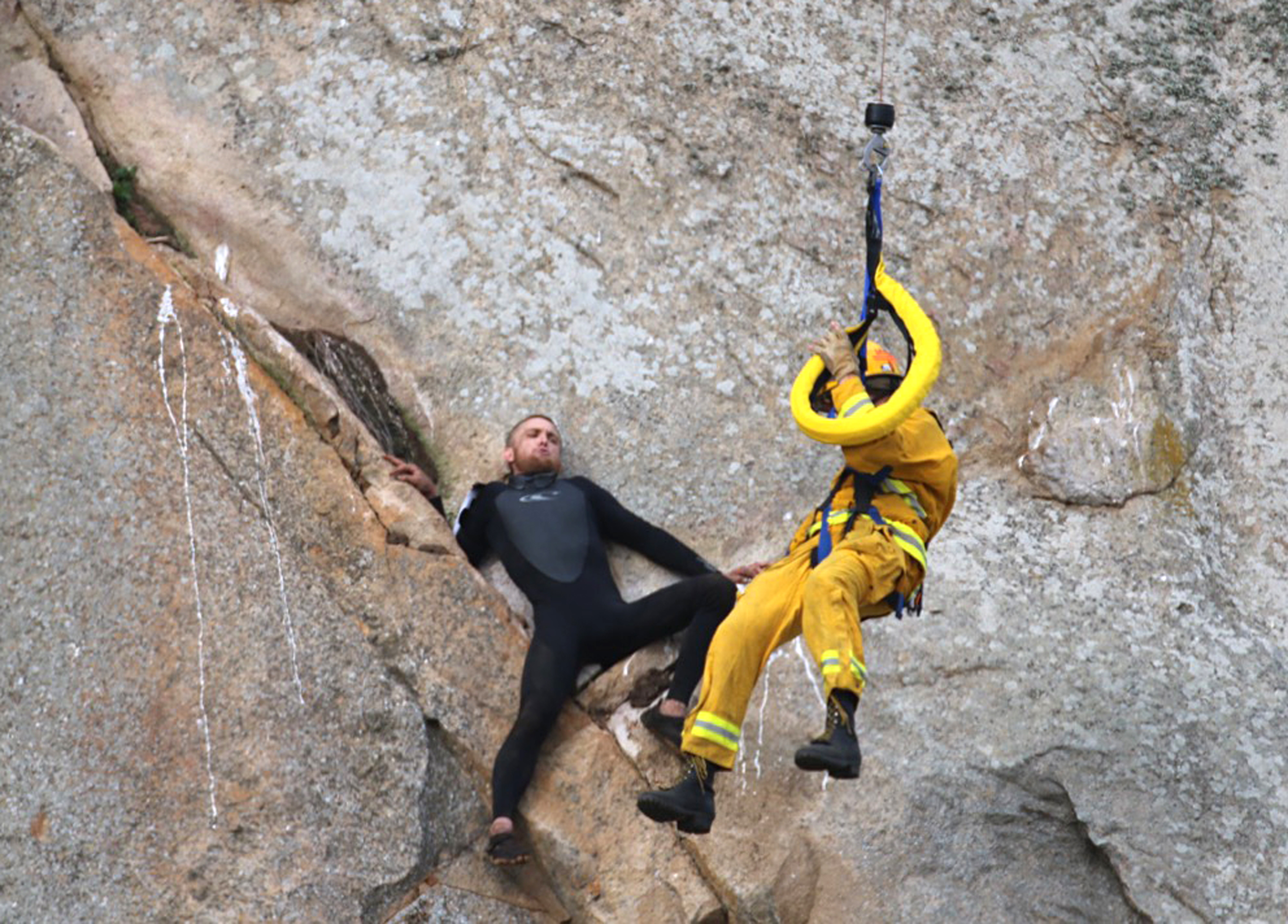 In this photo provided by Bob Isenberg, Michael Banks is stranded on a ledge some 80 feet off the ground on Morro Rock, a landmark in Morro Bay, Calif., on Thursday, April 7, 2016.