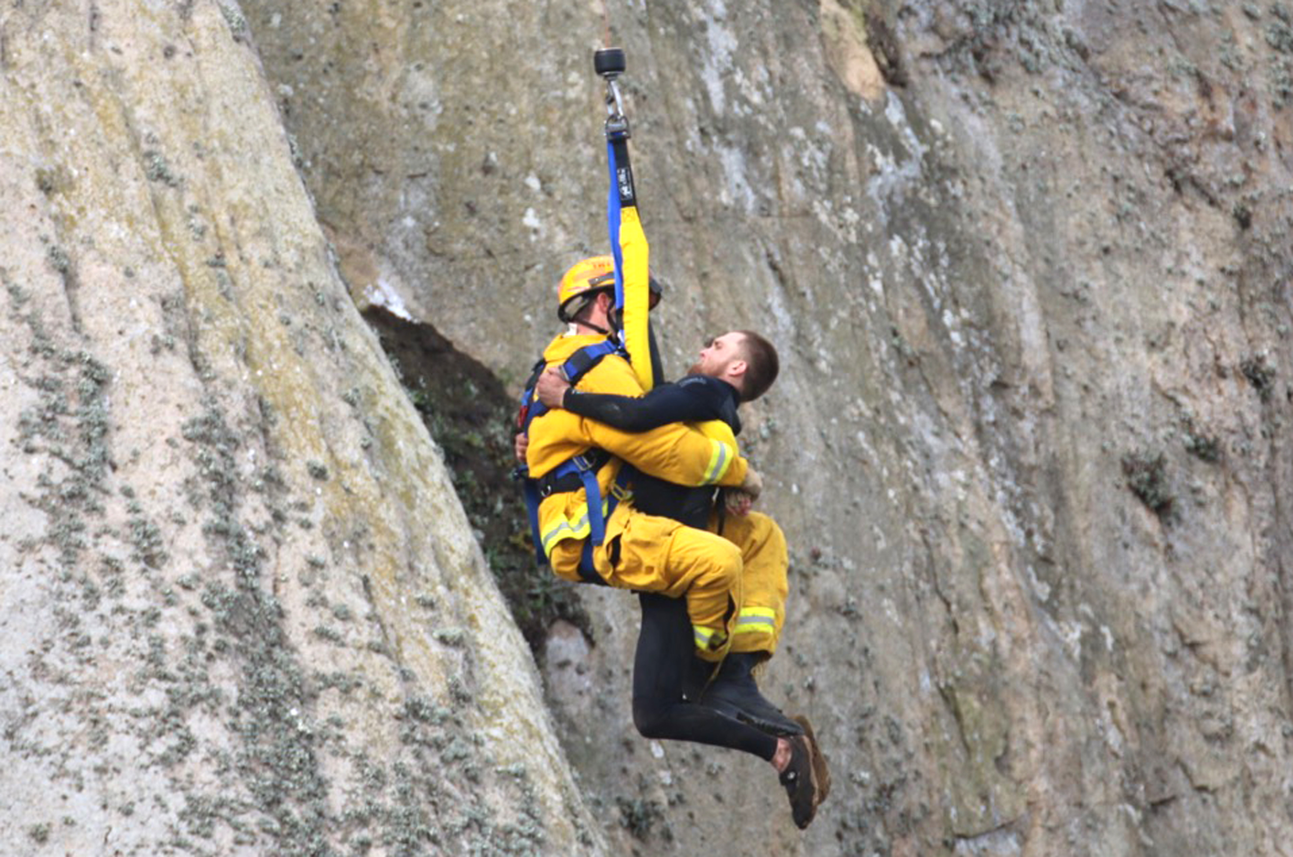 In this photo provided by Bob Isenberg, Michael Banks is rescued after being stranded on a ledge some 80 off the ground on Morro Rock, a landmark in Morro Bay, Calif., Thursday, April 7, 2016. He had scaled the rock to make an Internet proposal to his girlfriend - who said yes - but then got stuck on a ledge and couldn't get down. A helicopter had to be called, and Morro Bay Fire Department Capt. Todd Gailey was lowered by cable to pluck Banks and take him to safety.(Bob Isenberg via AP)