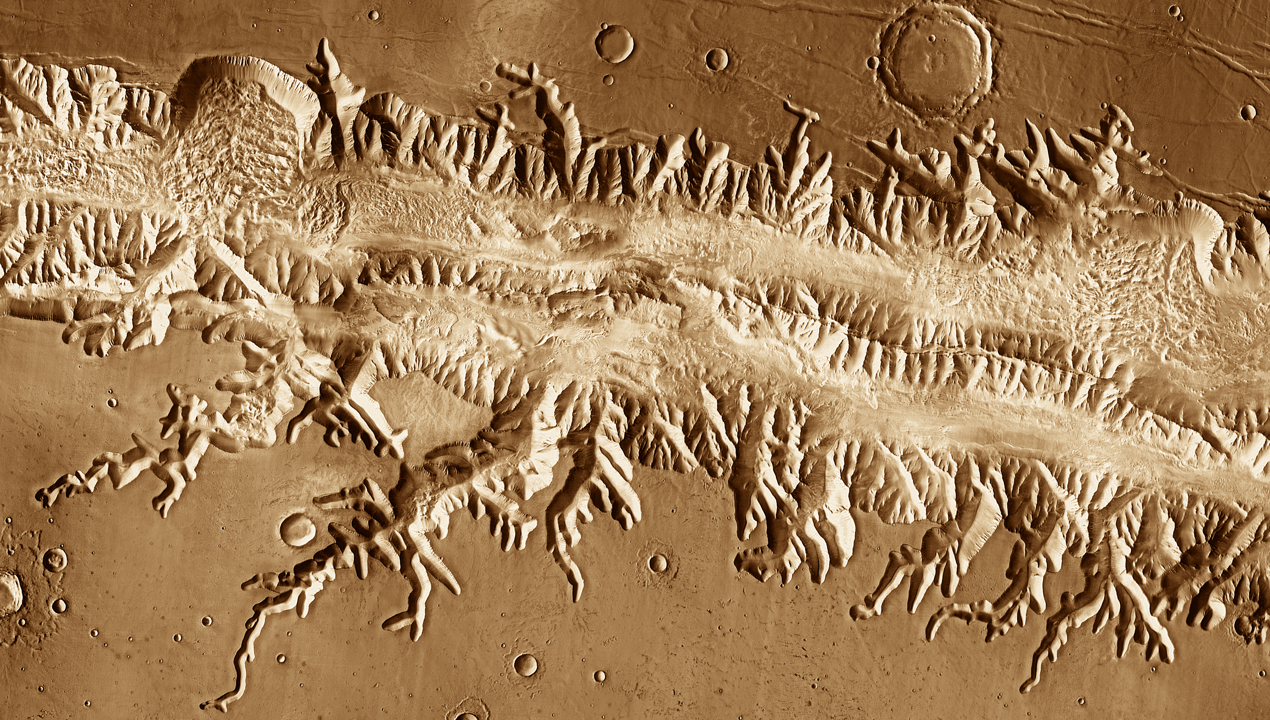 Valles Marineris:  With a length great enough to stretch from New York to Los Angeles, Valles Marineris is the Grand Canyon of Mars.  Scientists think the canyons cutting into the rim developed as subsurface water escaped and the ground collapsed, a process called  sapping.   This image was acquired in July 2005   by the Thermal Emission Imaging System instrument on NASA's Mars Odyssey orbiter.