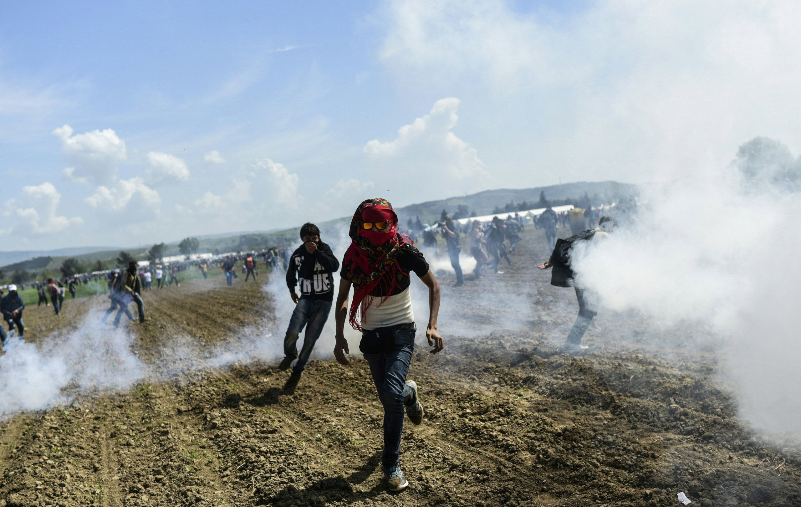 Refugees and migrants flee the tear gas as they clash with Macedonian police during a  protest to reopen the border near their makeshift camp in the northern Greek border village of Idomeni, on April 10, 2016.