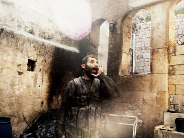 """SYRIA. Aleppo. 2013.  A rebel yells """"Allahu Akbar"""" (God is Great) during close-quarters fighting in Aleppo's Old City."""